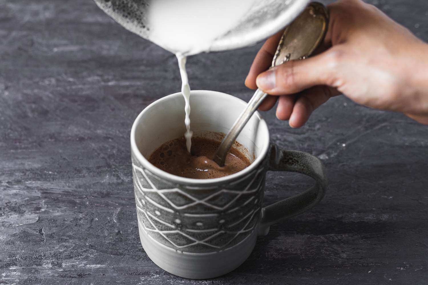 pouring milk into a cup of Instant Hot Cocoa Coffee
