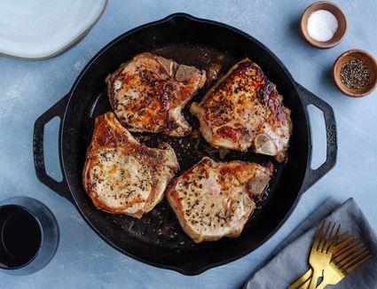 Pork chops frying in a skillet