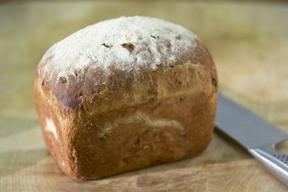 Home-baked, crusty loaf of bread with knife, close-up