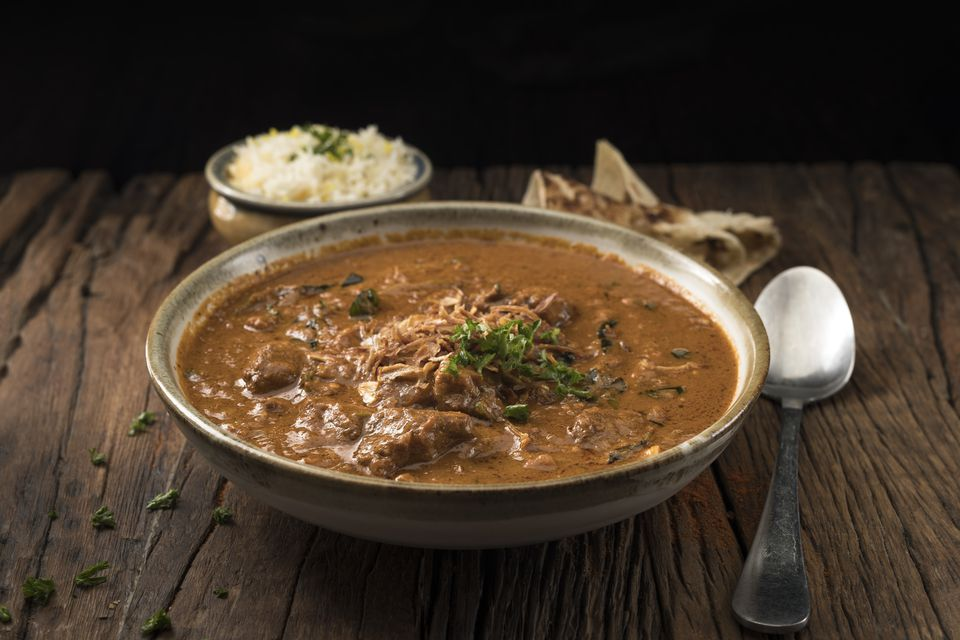 A Bowl of Lamb Curry Served With Naan Bread and Rice