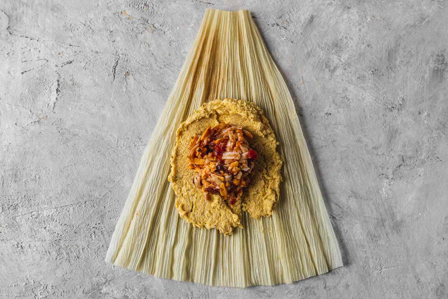 masa mixture and filling on top of a corn husk