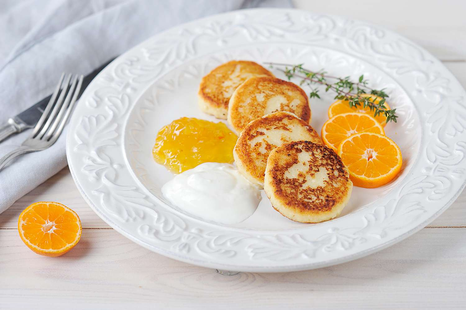 Cheesecakes with citrus jam and sour cream on a white plate. Next to the plate is a cloth napkin and cutlery. The composition is complemented by slices of mandarin.