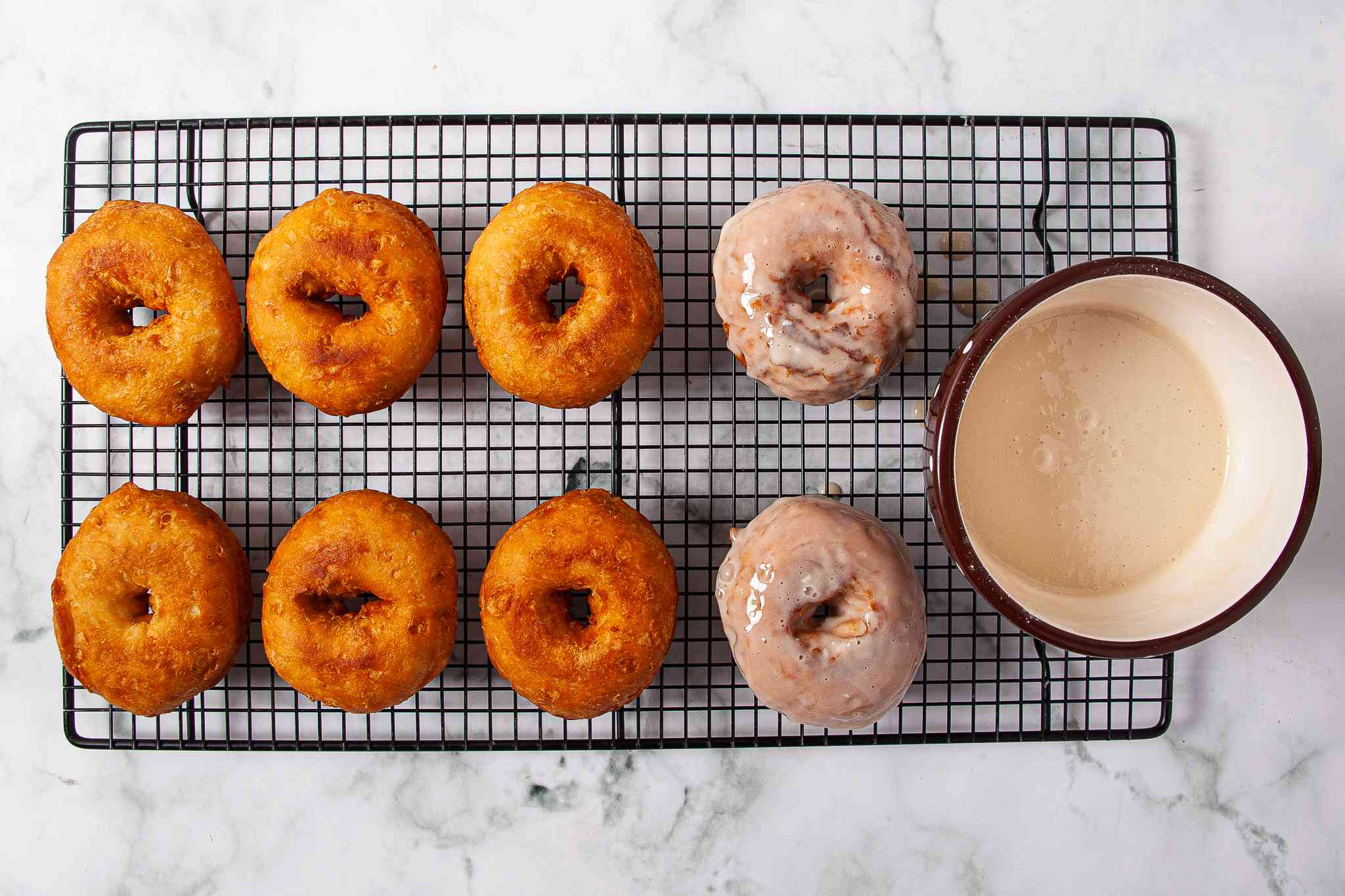 Doughnuts dipped in maple glaze on a cooling rack