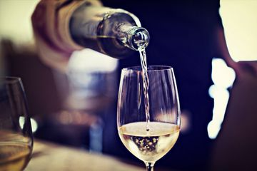 Midsection Of Waiter Pouring Wine In Glass At Restaurant