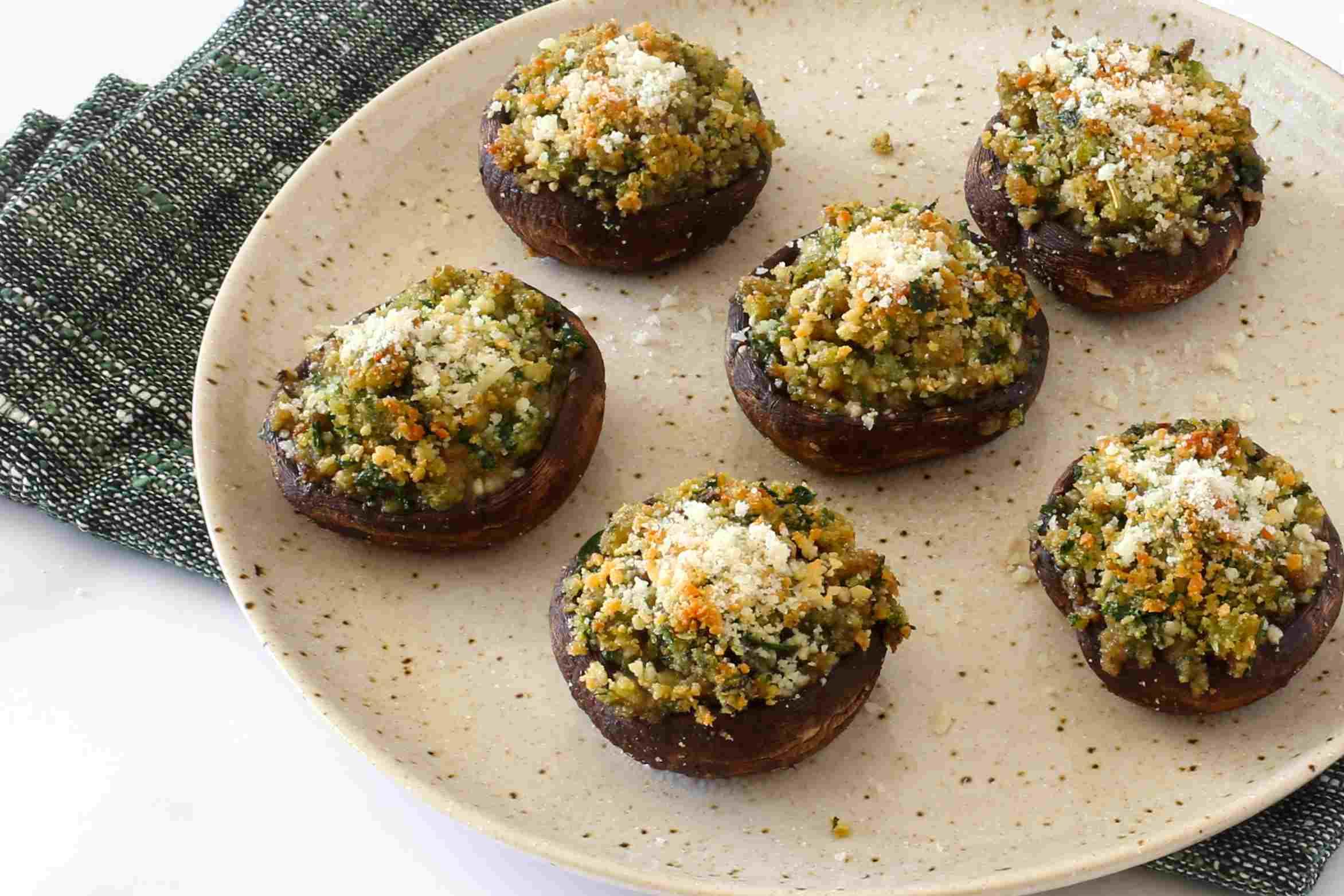 Arrange the stuffed mushrooms on a plate.