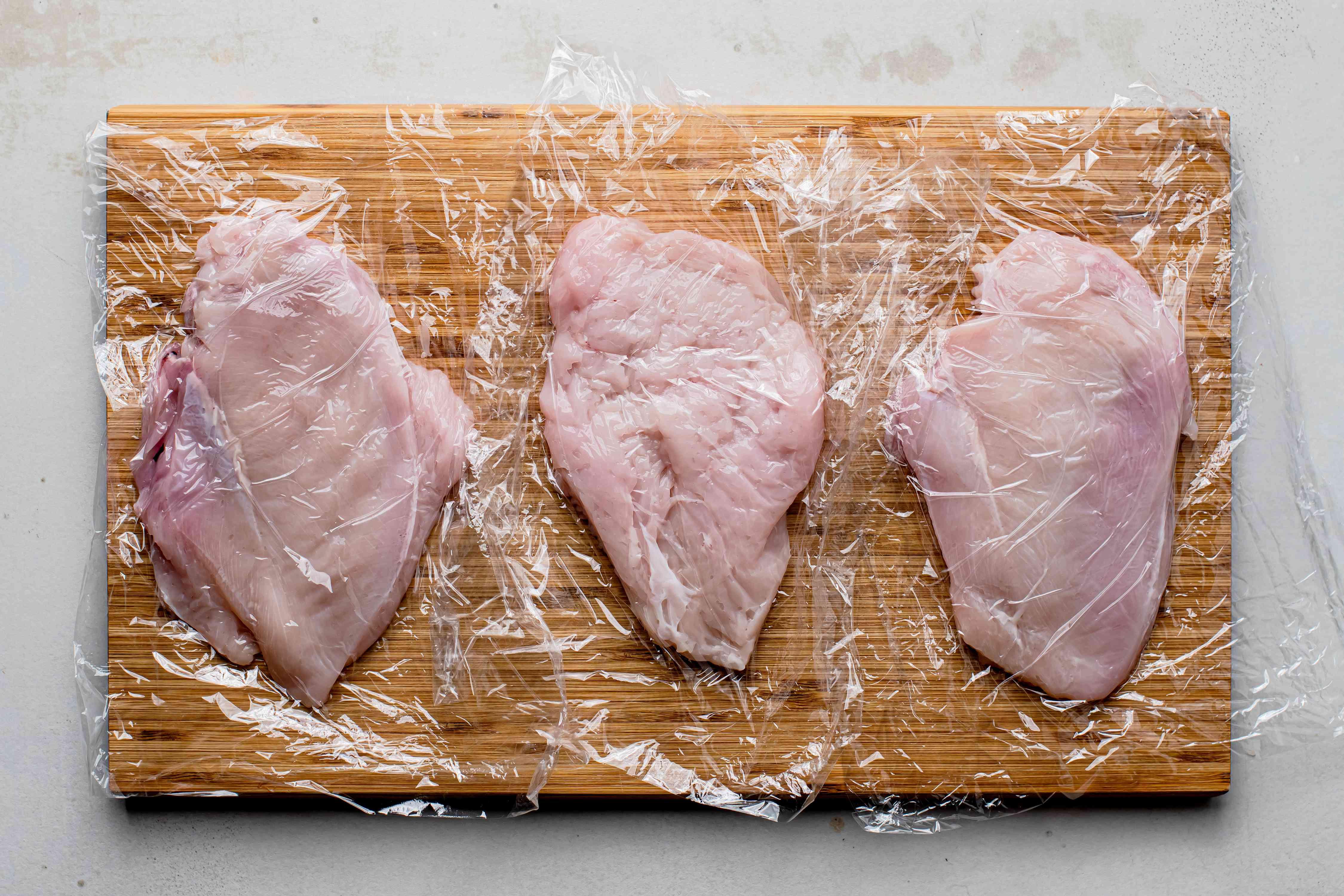 Chicken in plastic wrap on a wooden board