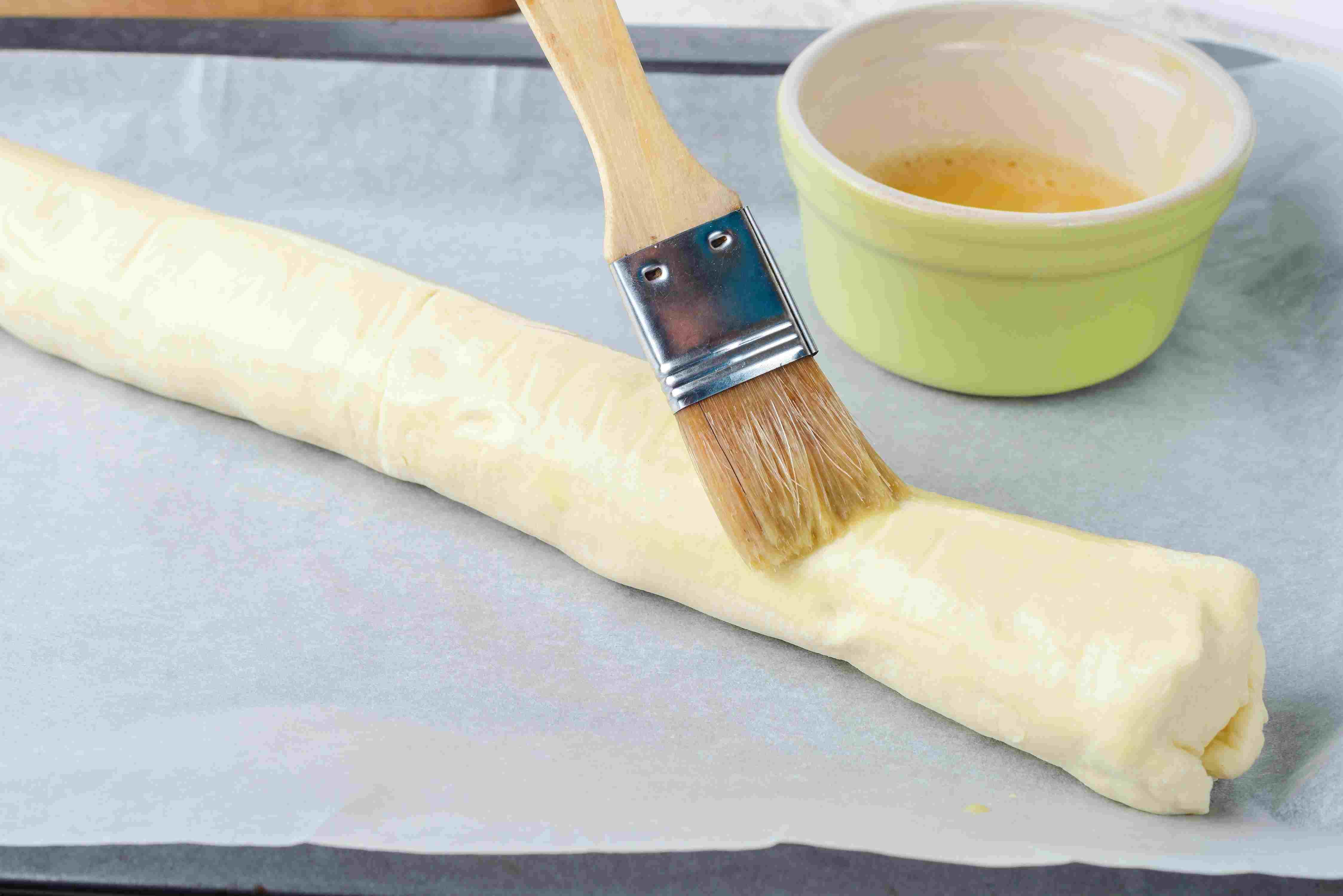 pastry brush brushing beaten egg on seam