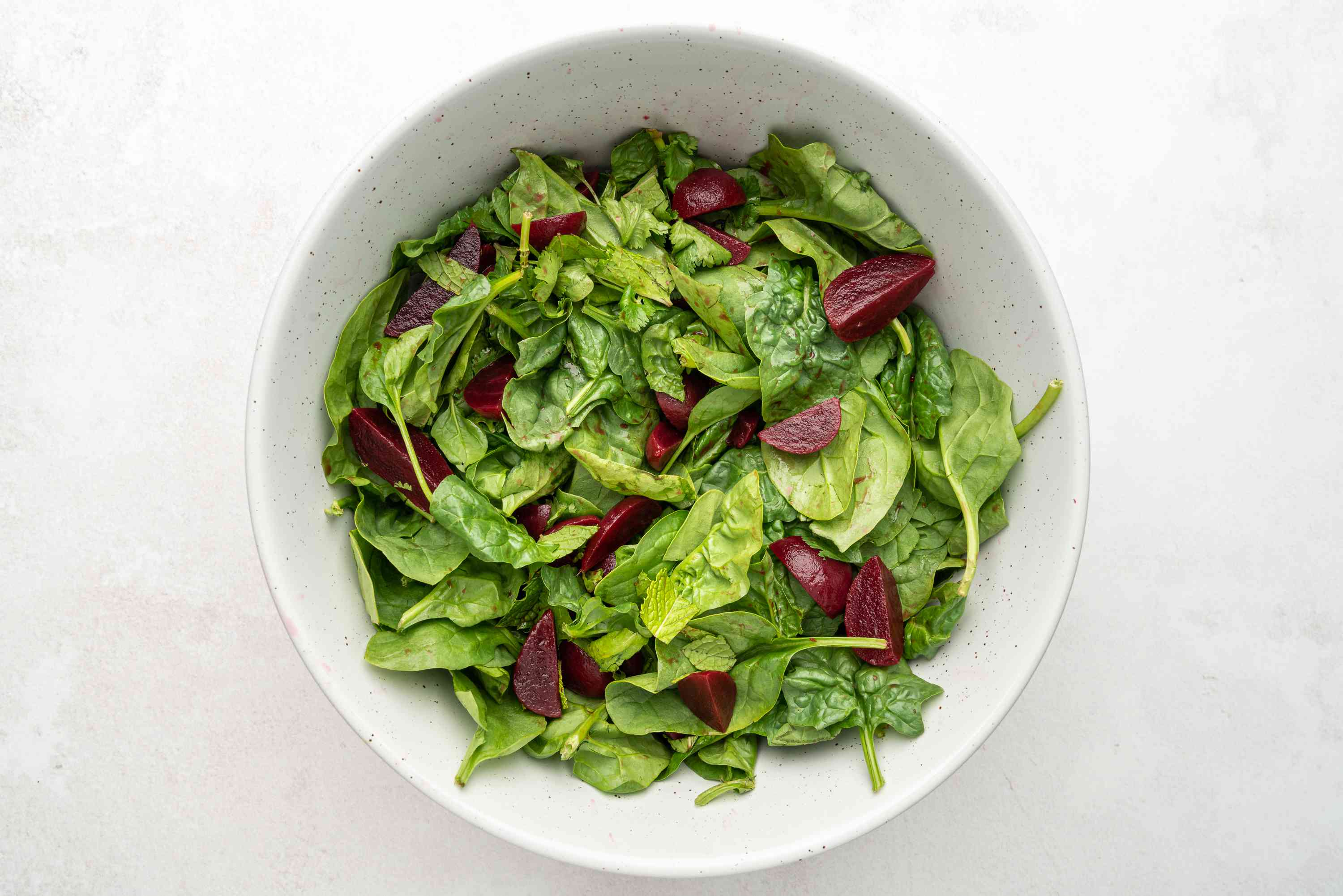 Mix together the beetroot wedges, the spinach, and most of the chopped mint and coriander in a large serving bowl