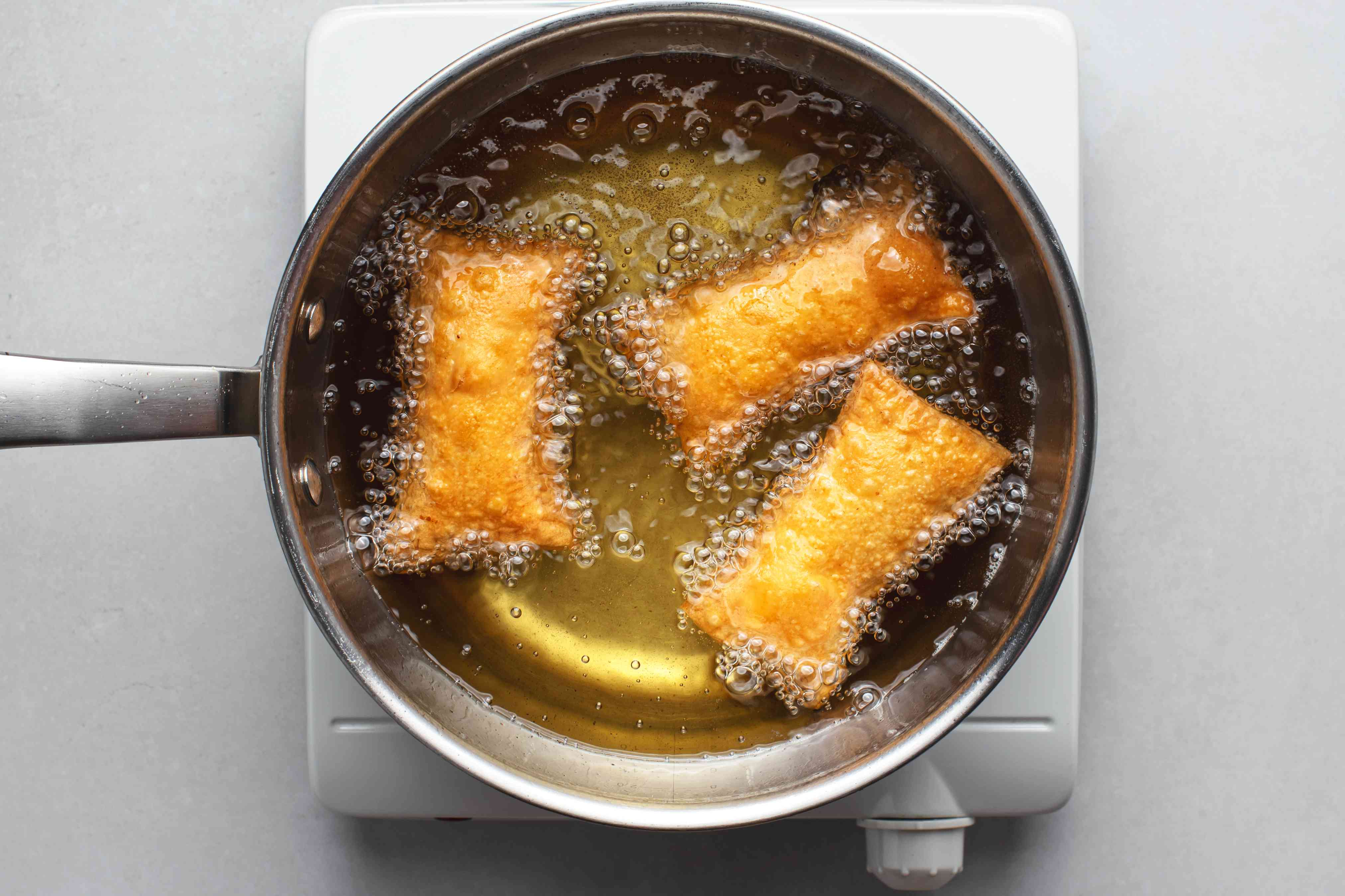Pasteles frying in a pot of oil
