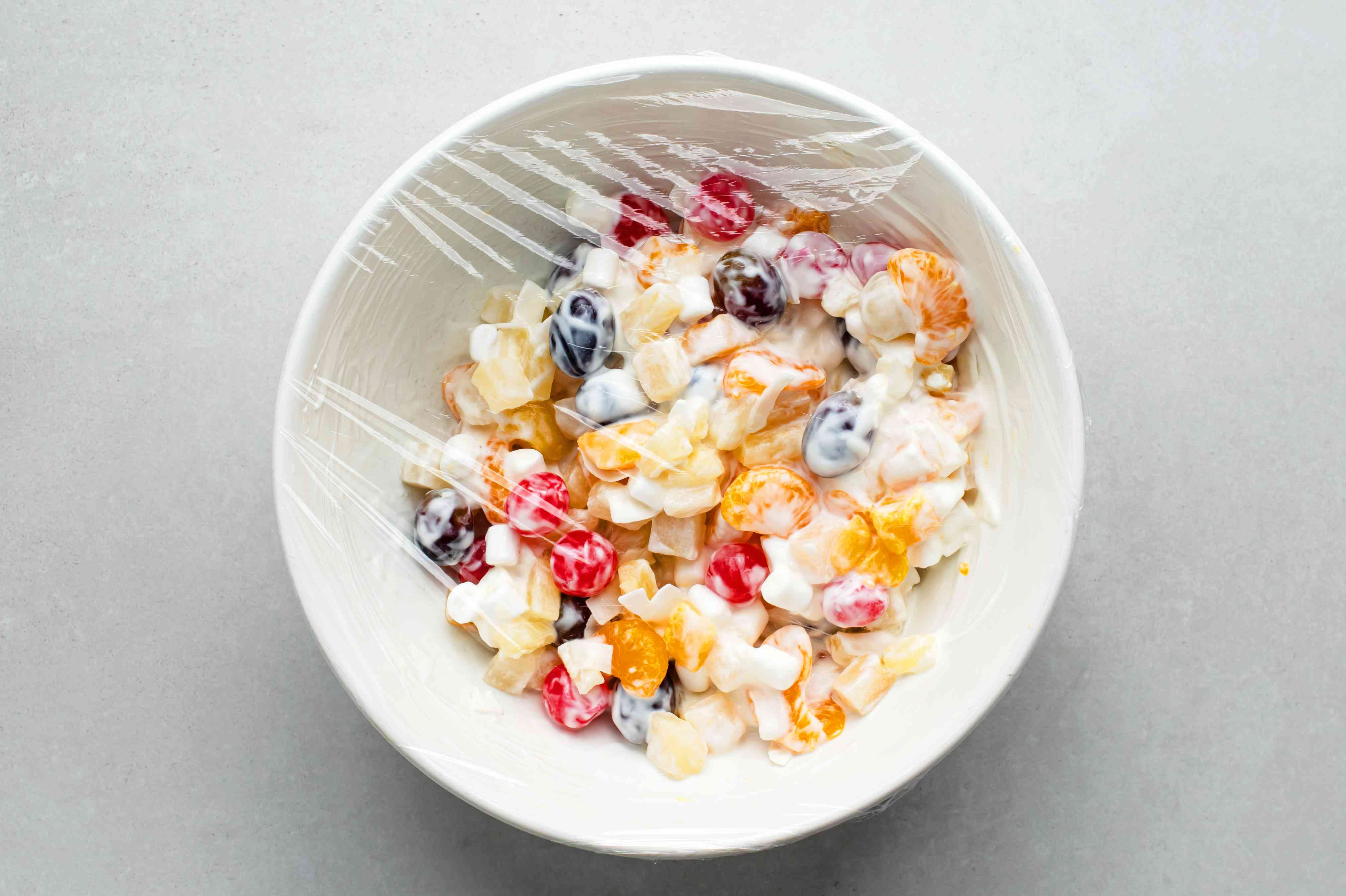 fruit salad in a bowl wrapped with plastic wrap