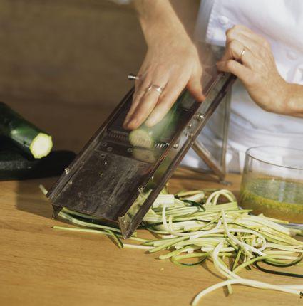 Slicing a zucchini using a kitchen mandoline