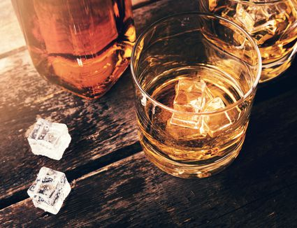 Bottle of whiskey with full glasses and ice cubes