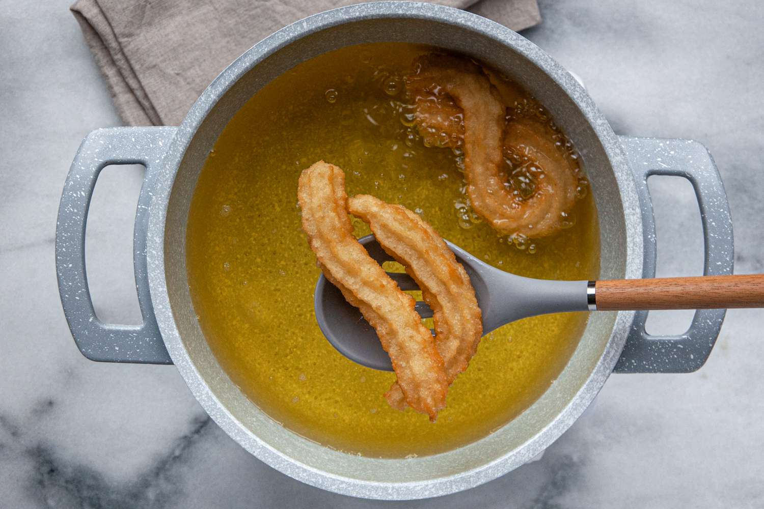 Churros on a slotted spoon above a pot of oil