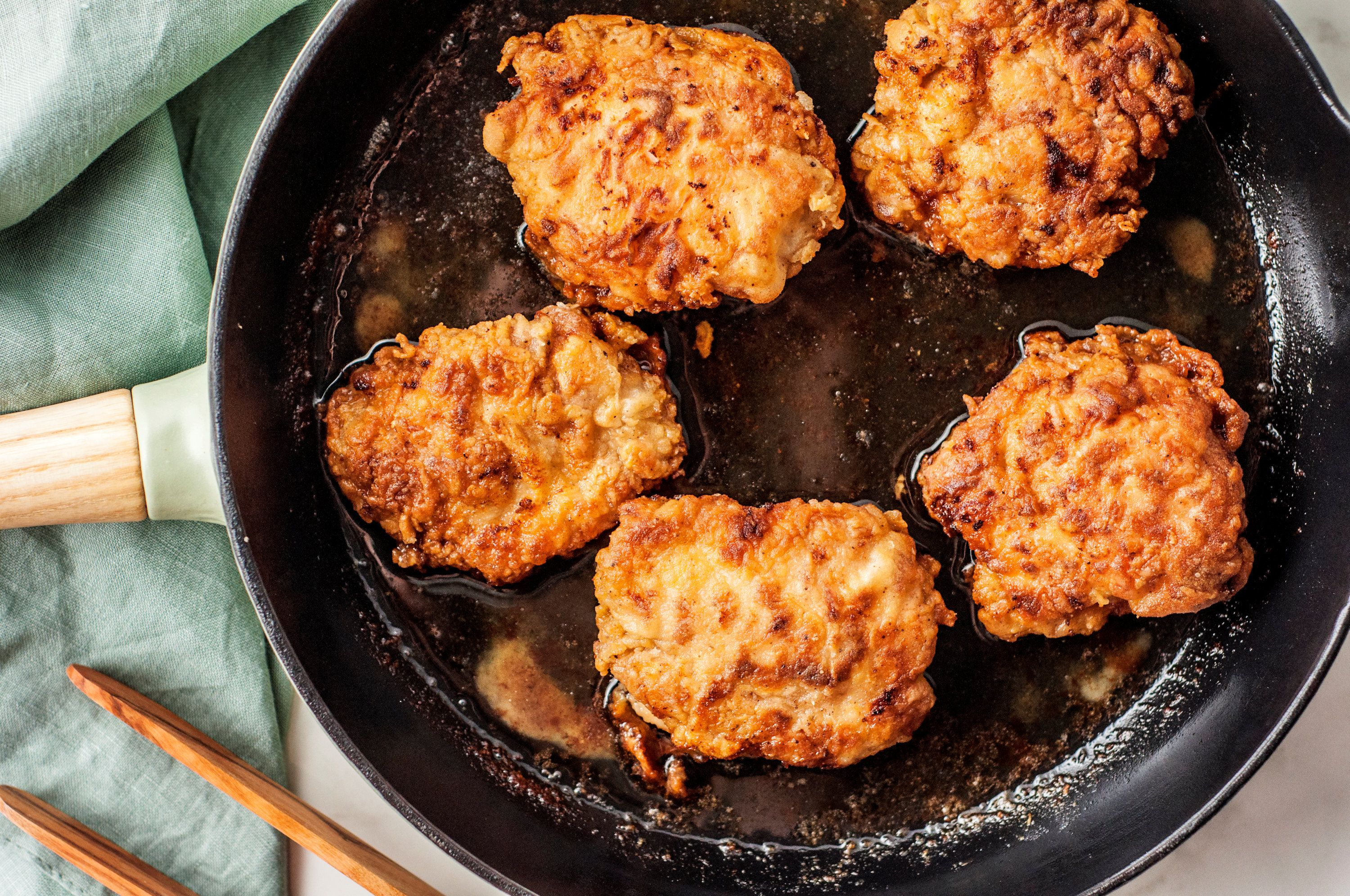 Chicken thighs being fried in oil