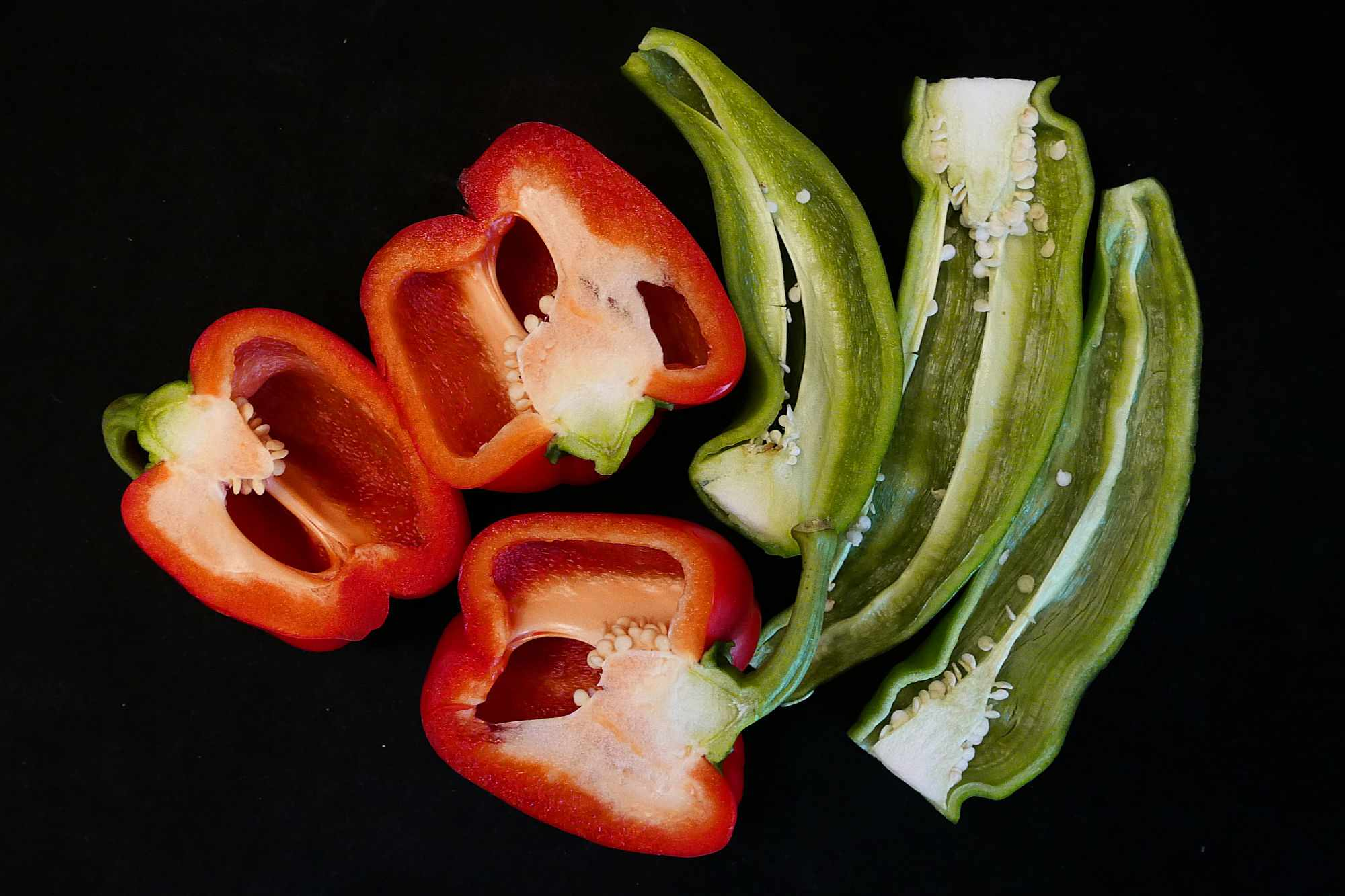 Peppers cut in half against black background.