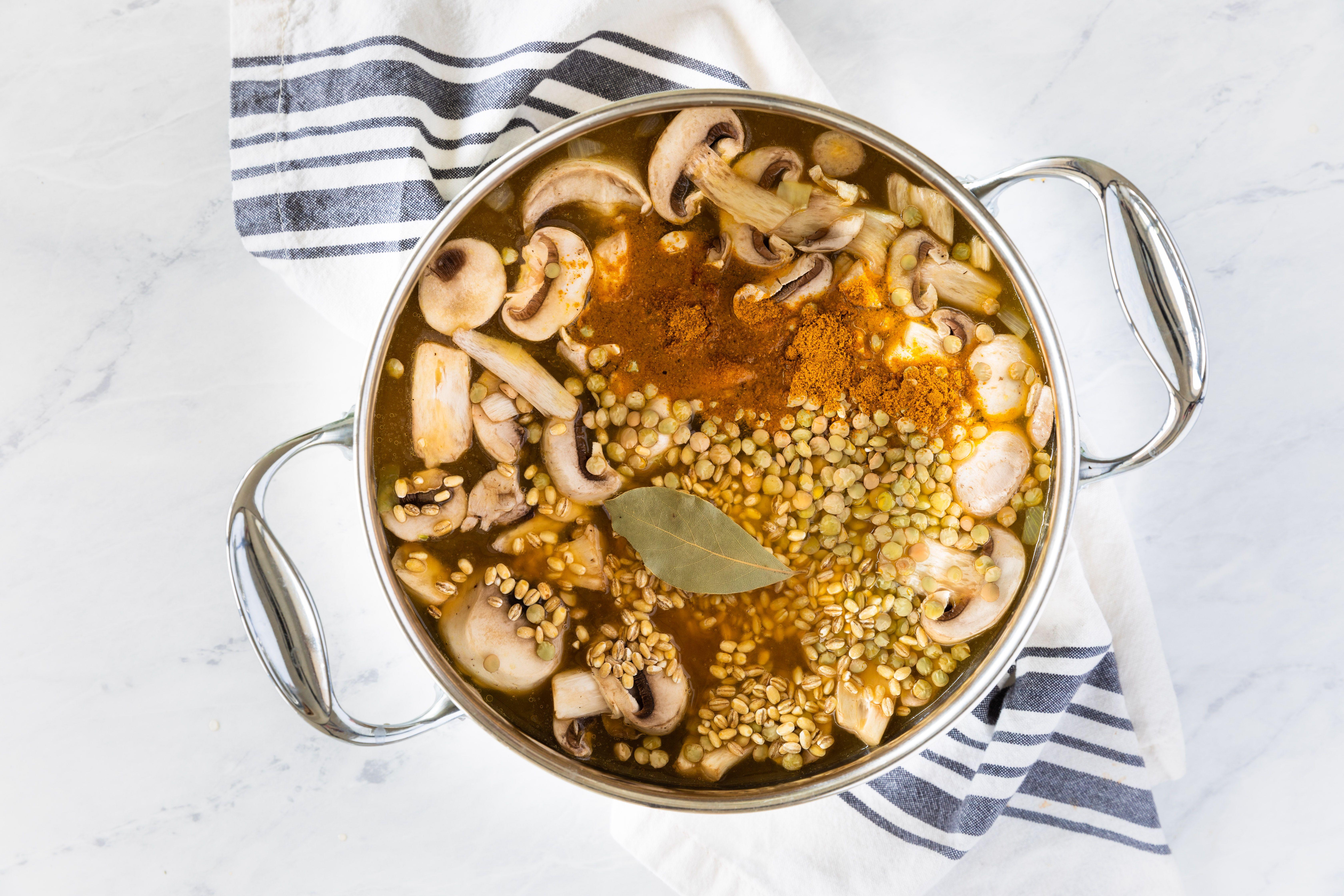 Vegetable broth, mushrooms, lentils, bay leaf, and seasoning in saucepan