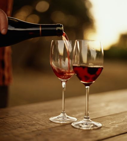 Hand pouring red wine into glass - stock photo