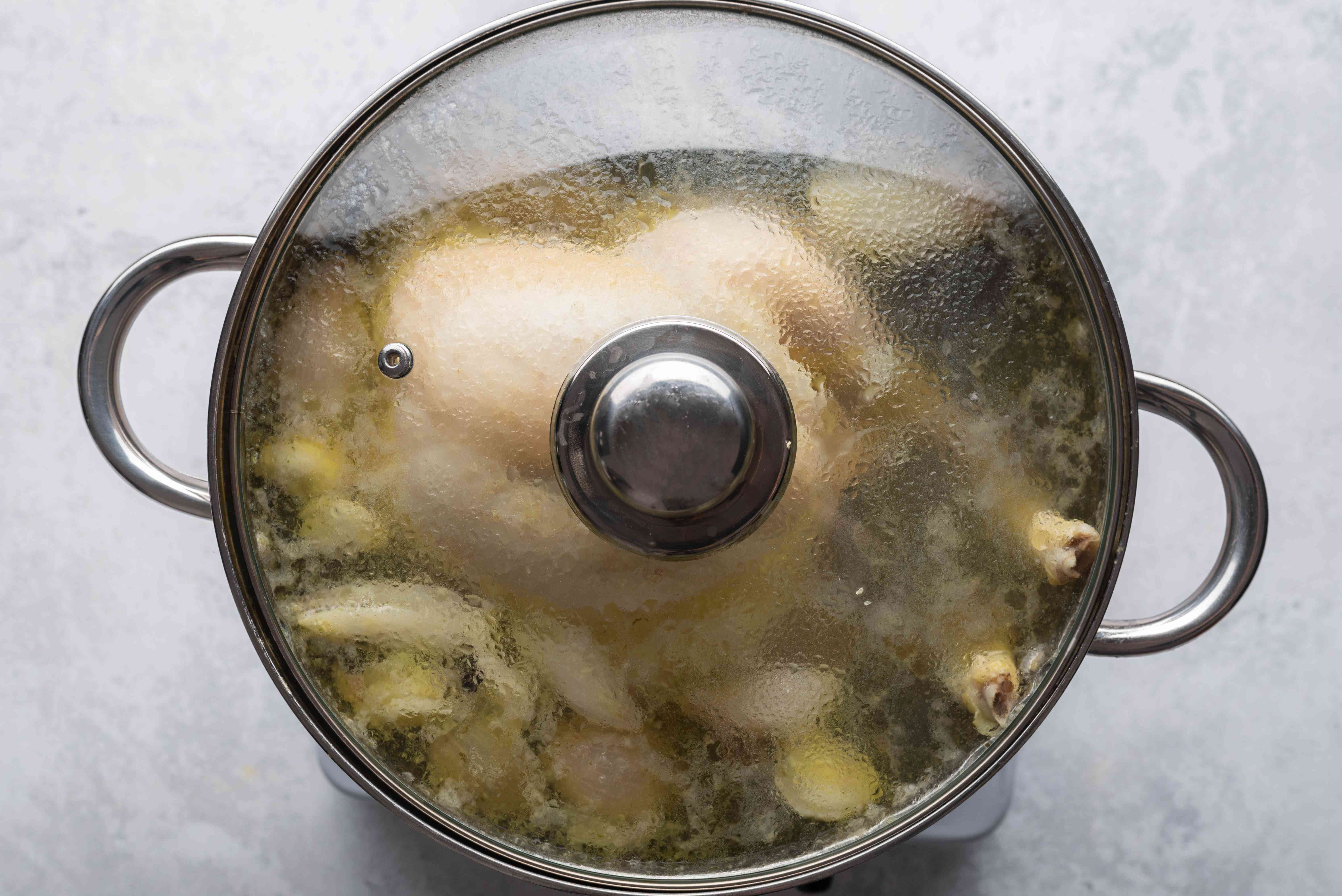 chicken cooking in a covered pot
