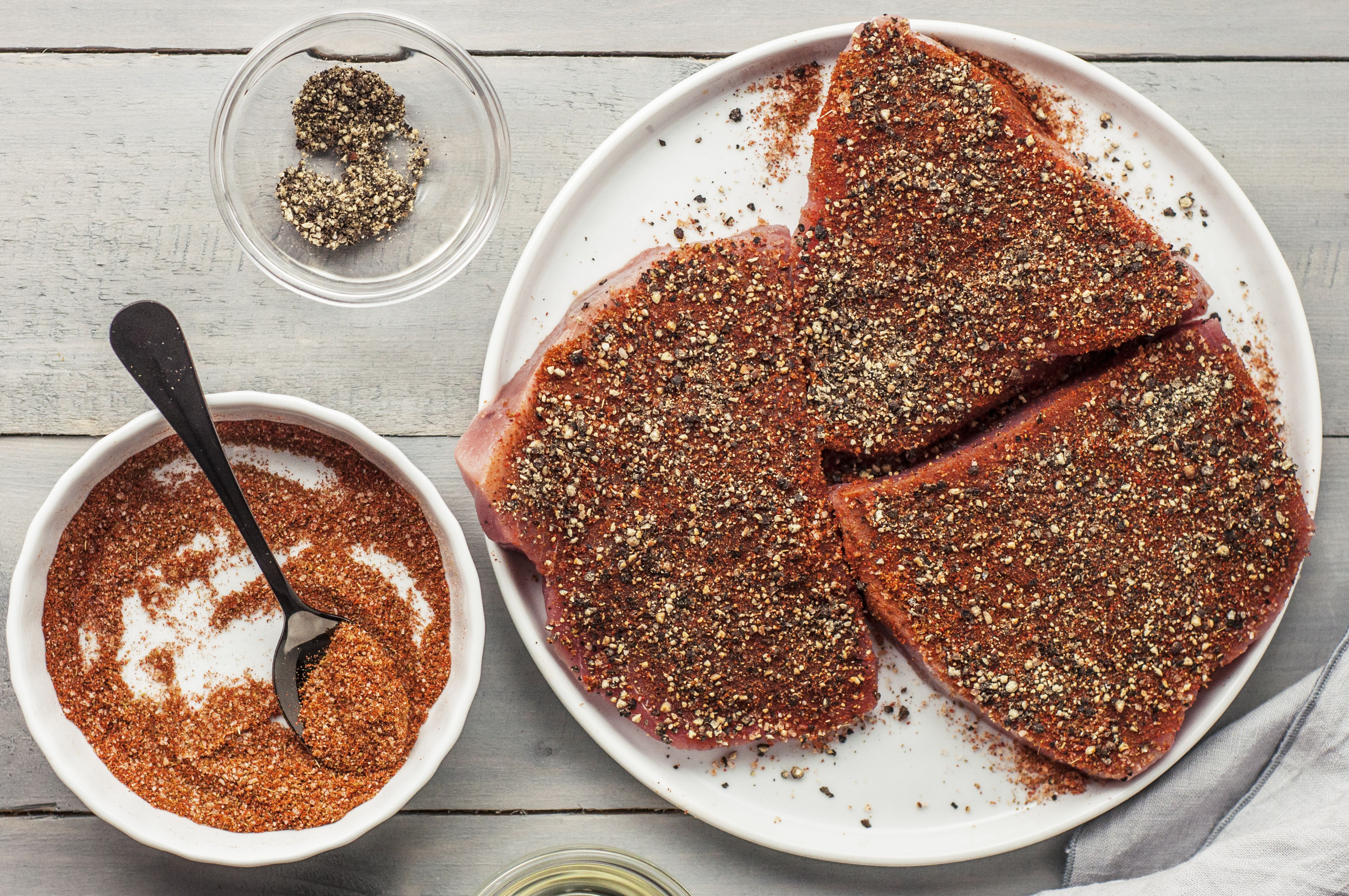 Evenly coat the tuna steaks with the freshly ground black pepper