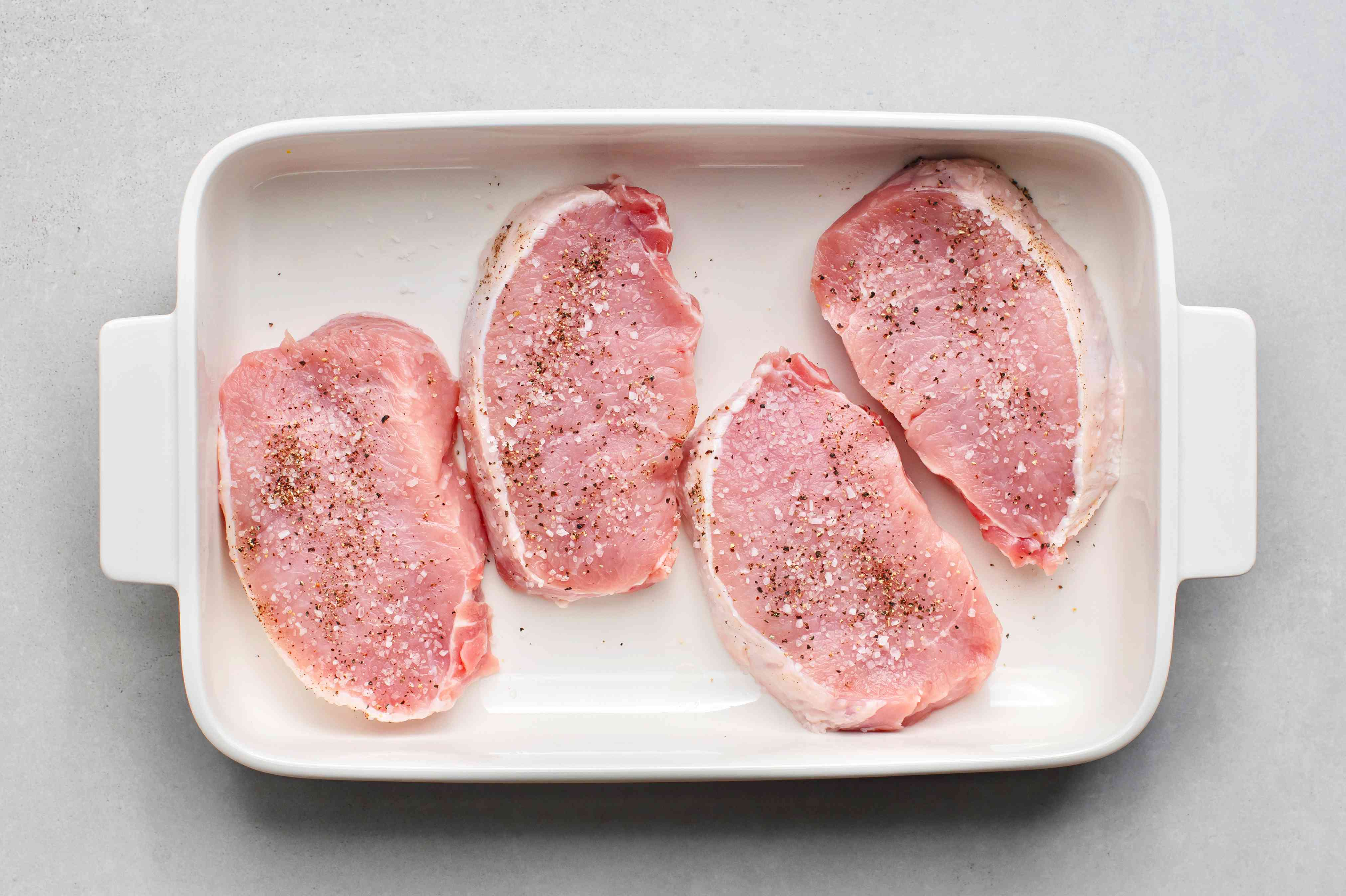 Pork chops in a baking dish sprinkled with salt and pepper