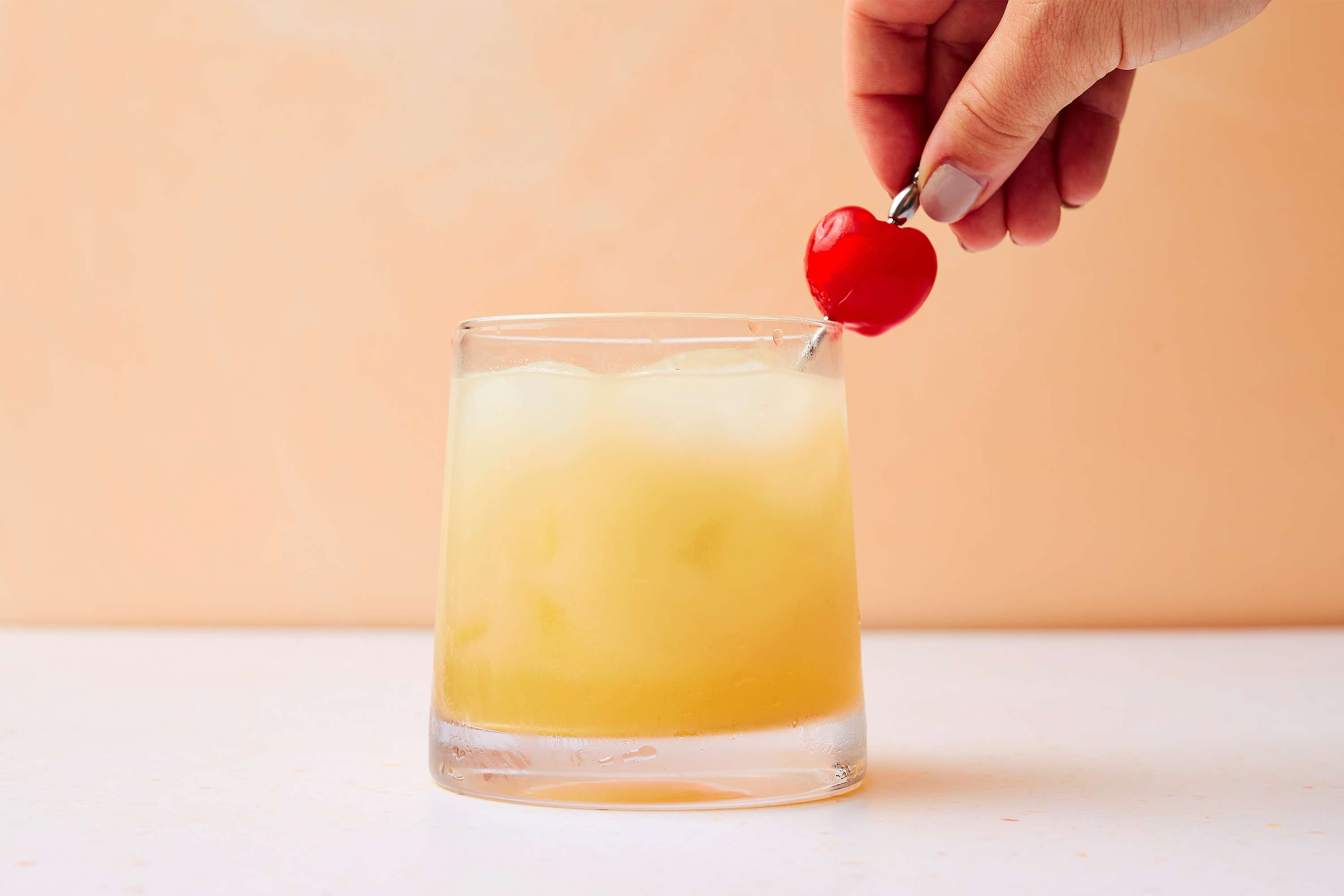 Apricot Sour Cocktail in a glass, garnished with a cherry