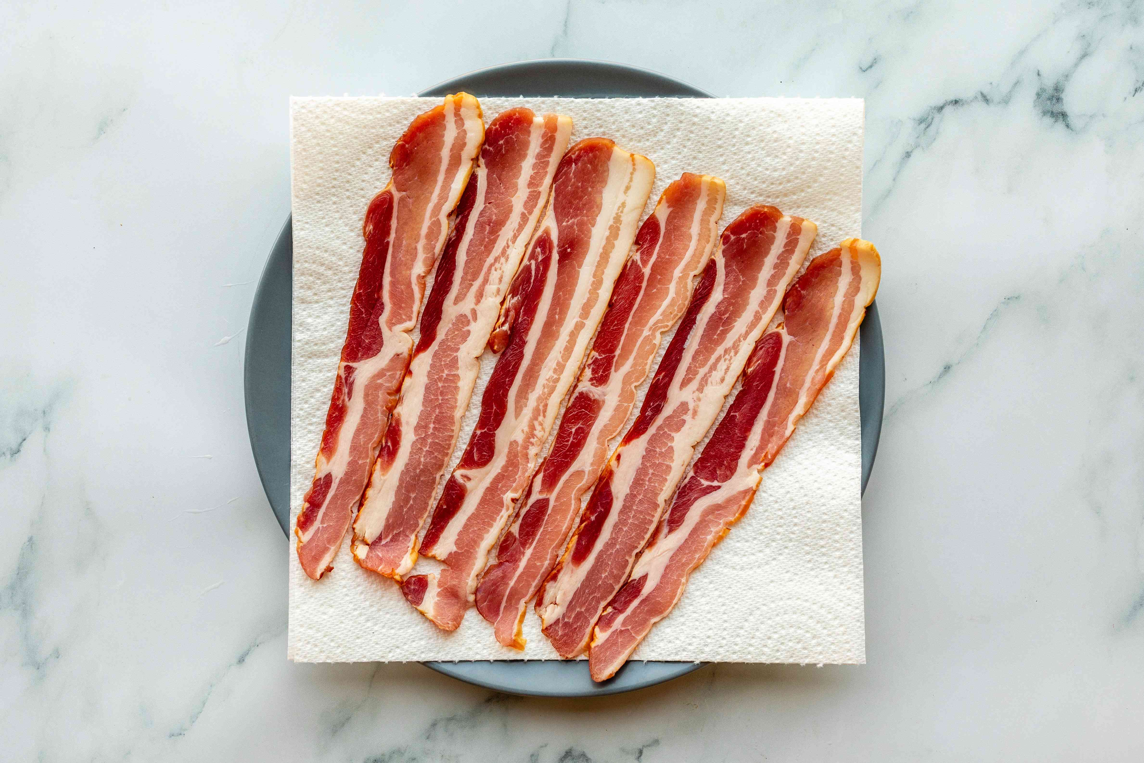 Six slices of bacon arranged on a paper towel and plate