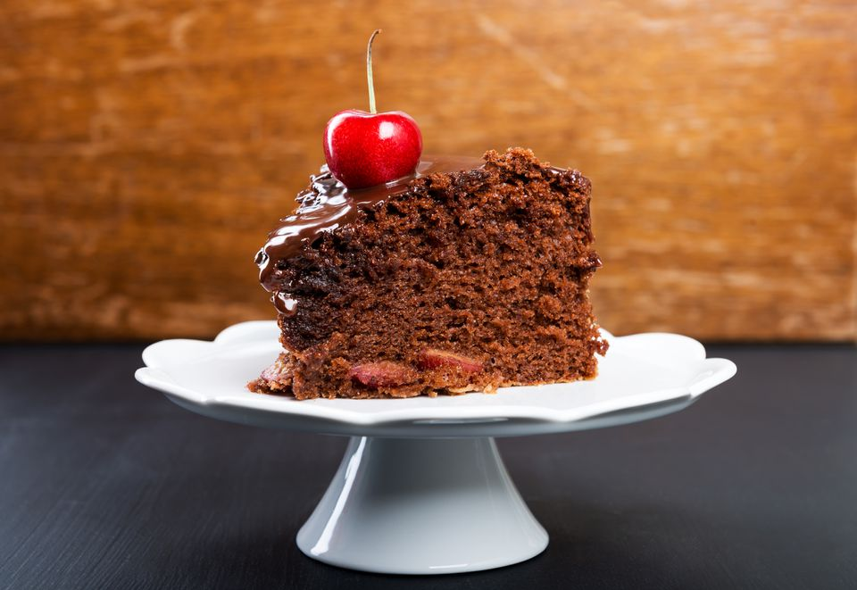 A slice of chocolate cherry cake on a cake stand