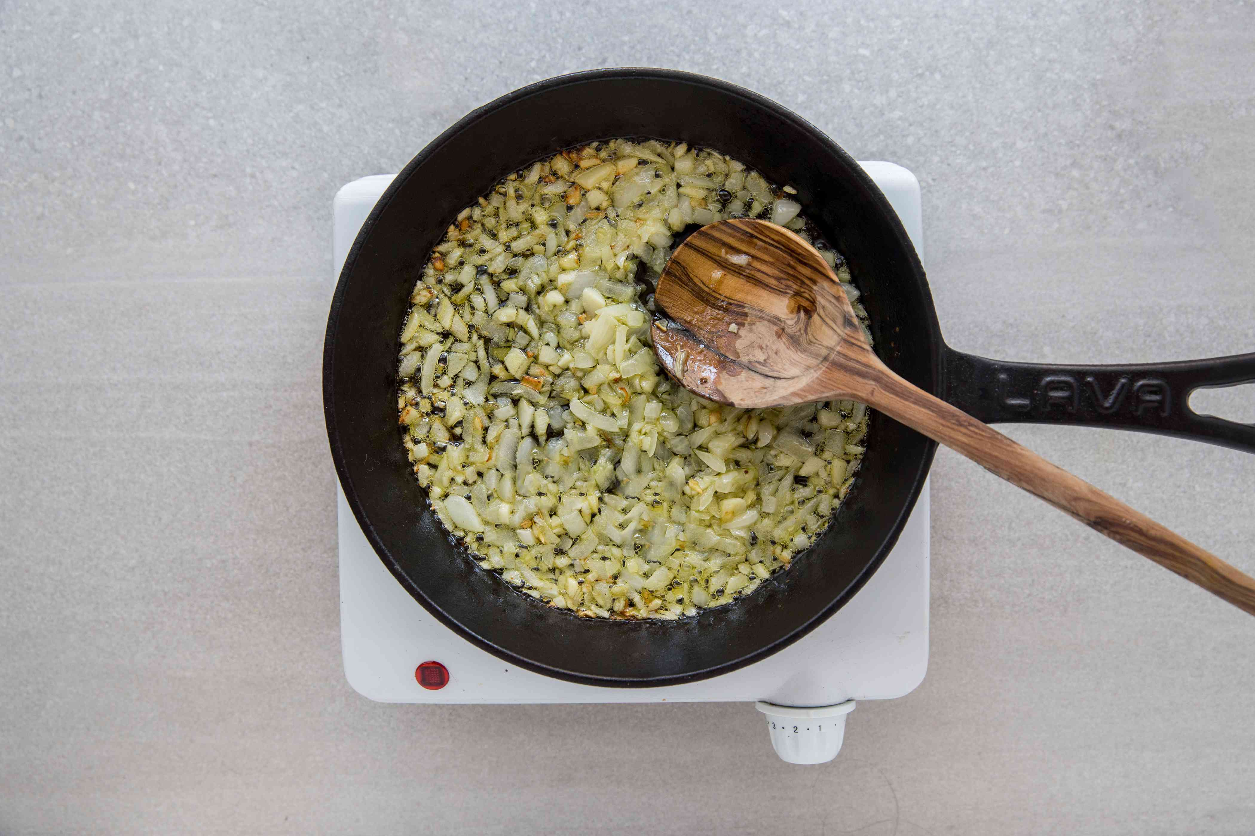 onions and garlic cooking in a cast iron pan