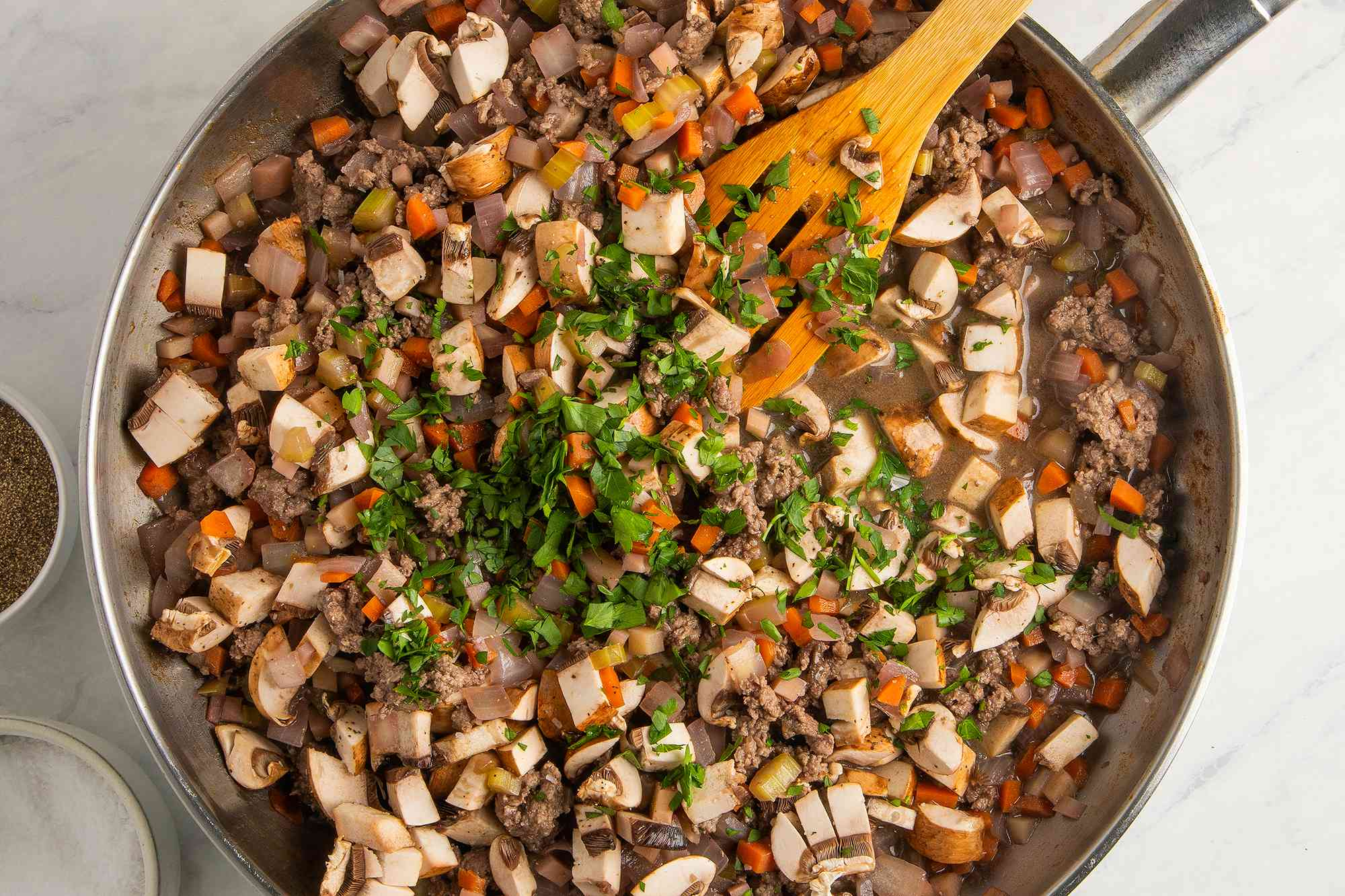 Add the remaining stock, mushrooms, and parsley to the pan with the meat and vegetables