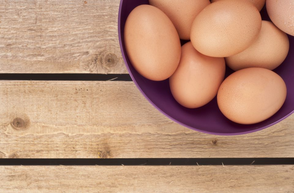 Hen's eggs in purple bowl on wooden background, close-up
