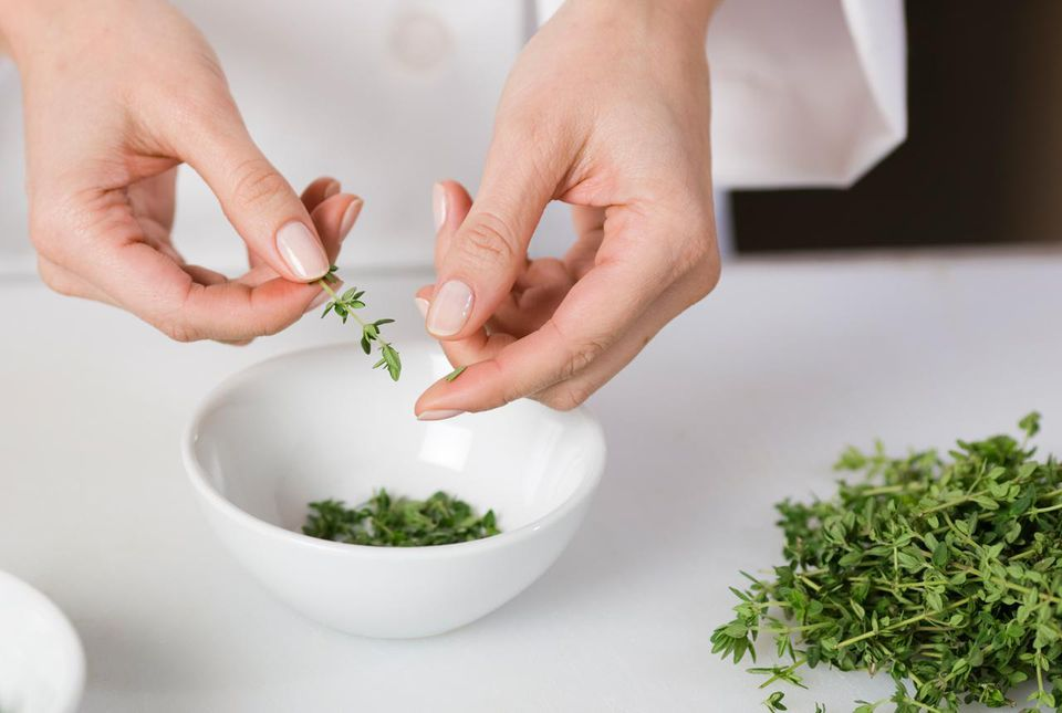Cook preparing fresh thyme