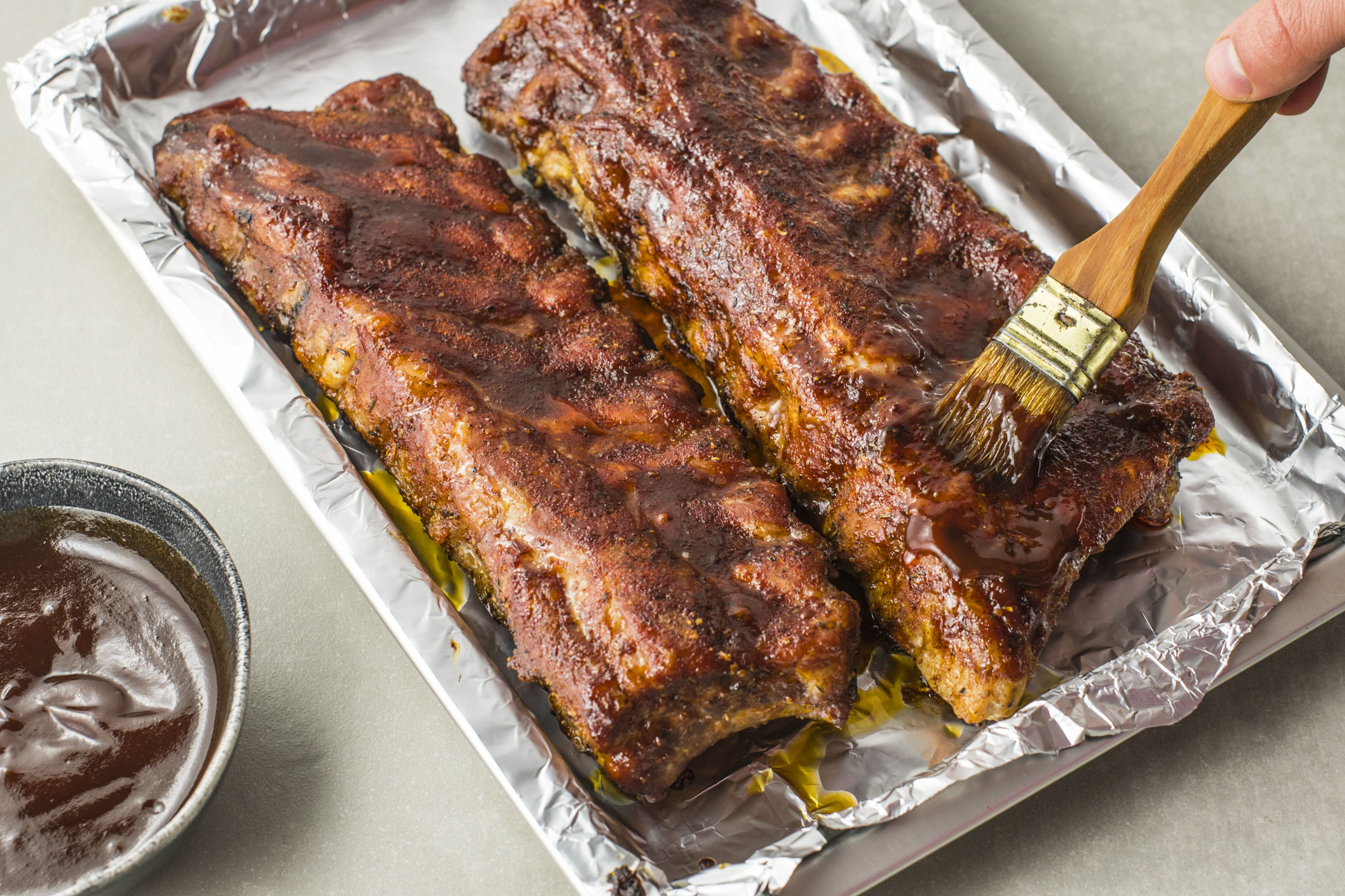 Cooked ribs being painted with more sauce