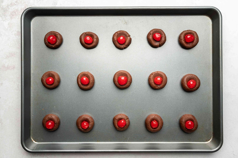 dough balls with cherries on top o na baking sheet