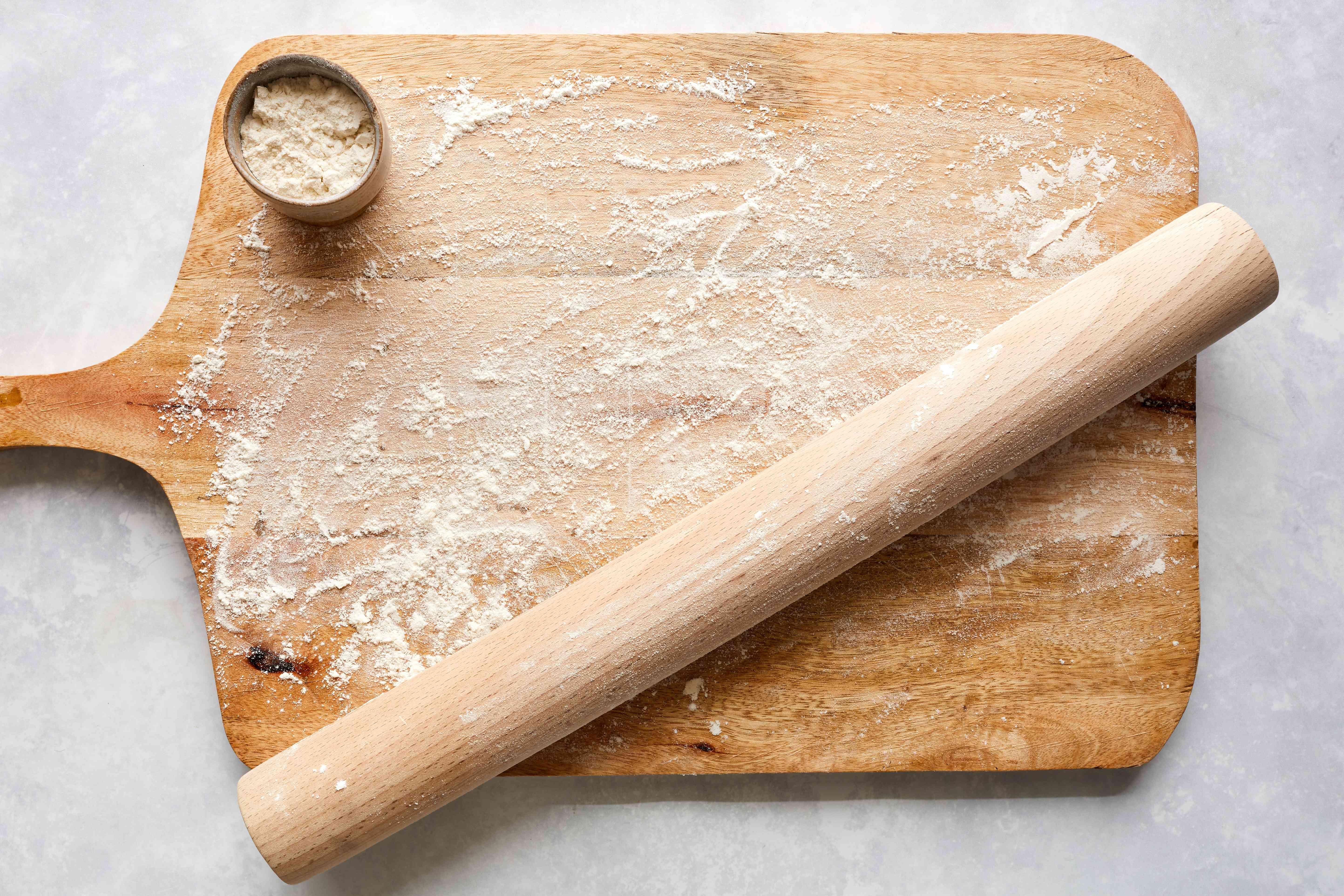 Floured wood board and wooden rolling pin