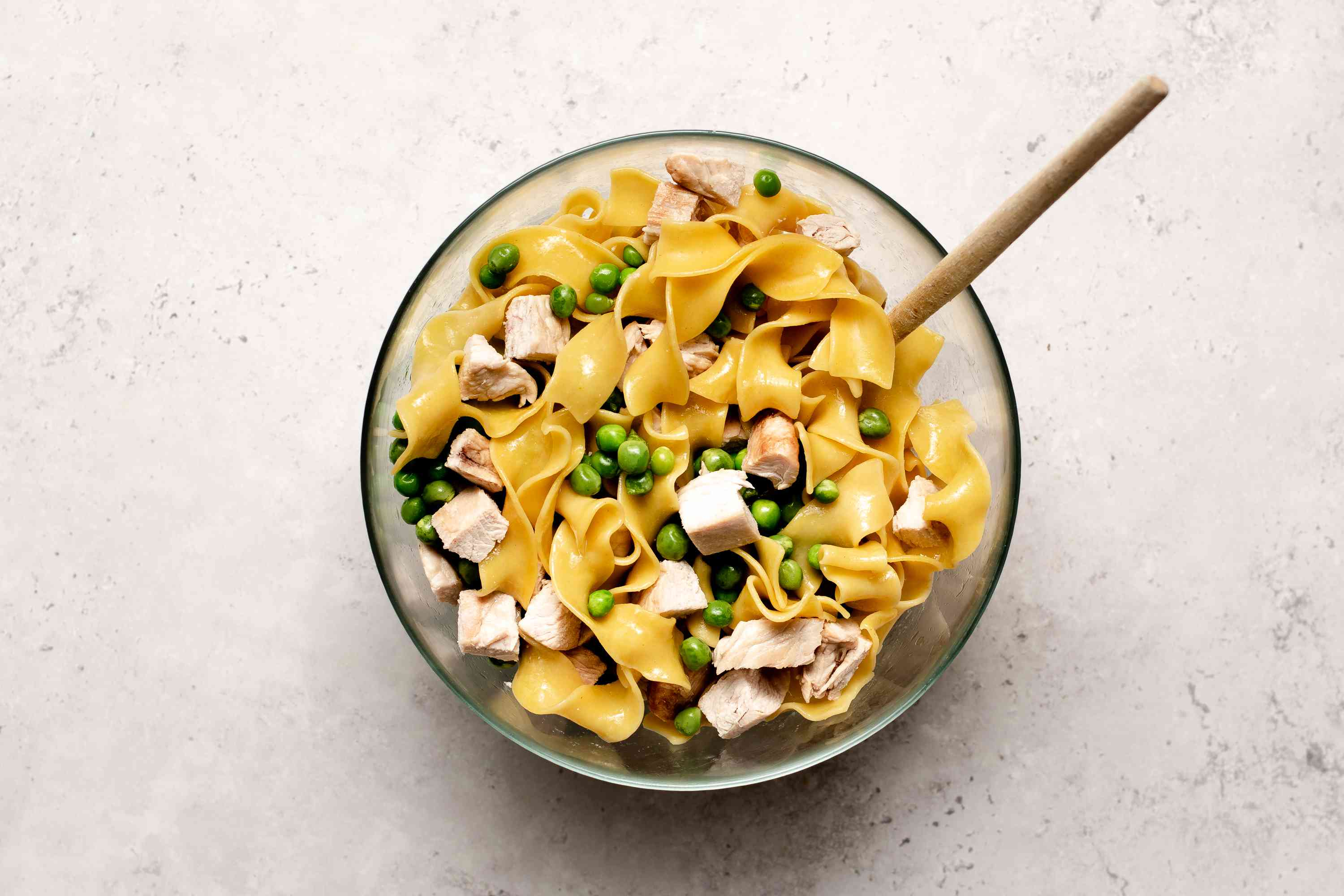 thawed peas in a large bowl with the diced cooked turkey and cooked noodles