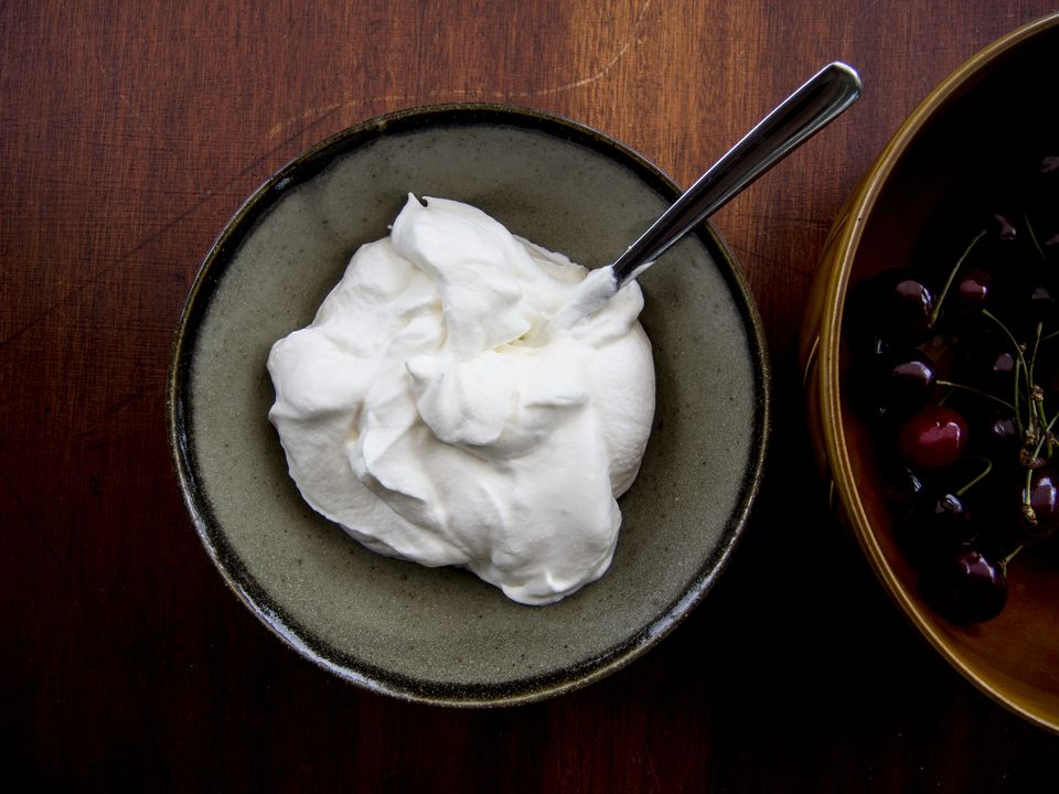 Cherries and Whipped cream in bowls on a wooden table