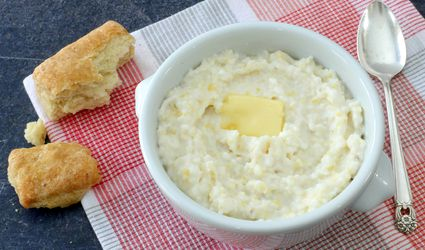 Grits in a bowl with butter and biscuits.