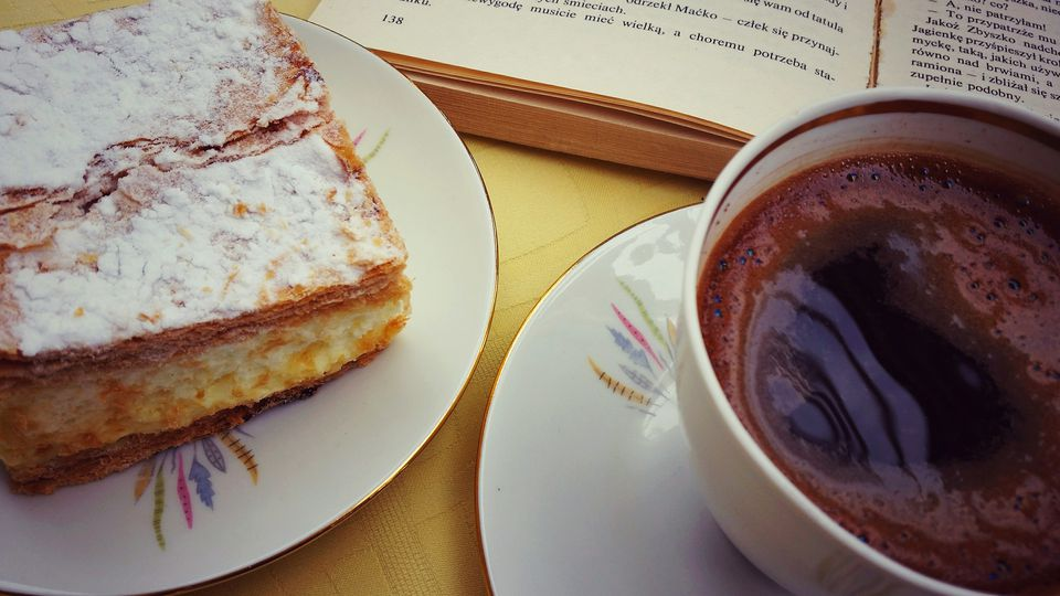 Close-Up Of Served Black Coffee With Gibanica Cake On Table