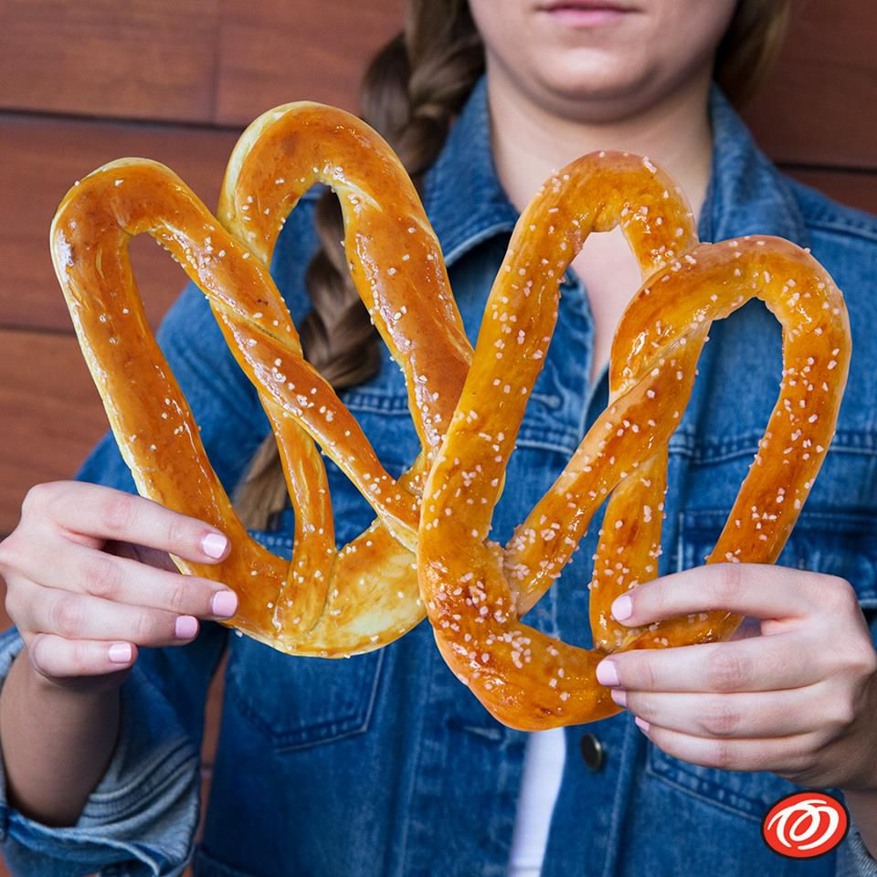A woman holding two pretzels