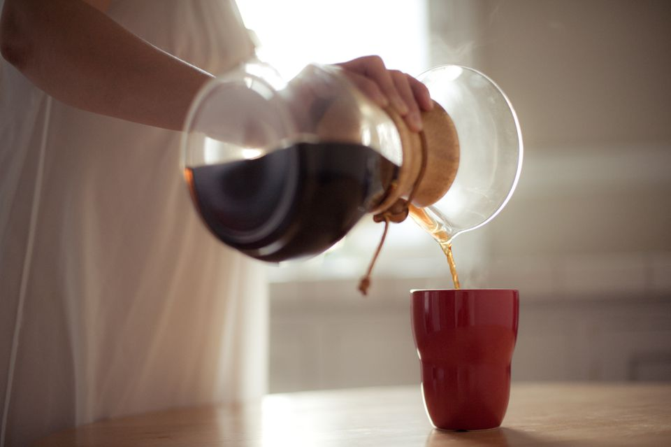 Man pouring coffee from pour over coffee maker into red cup
