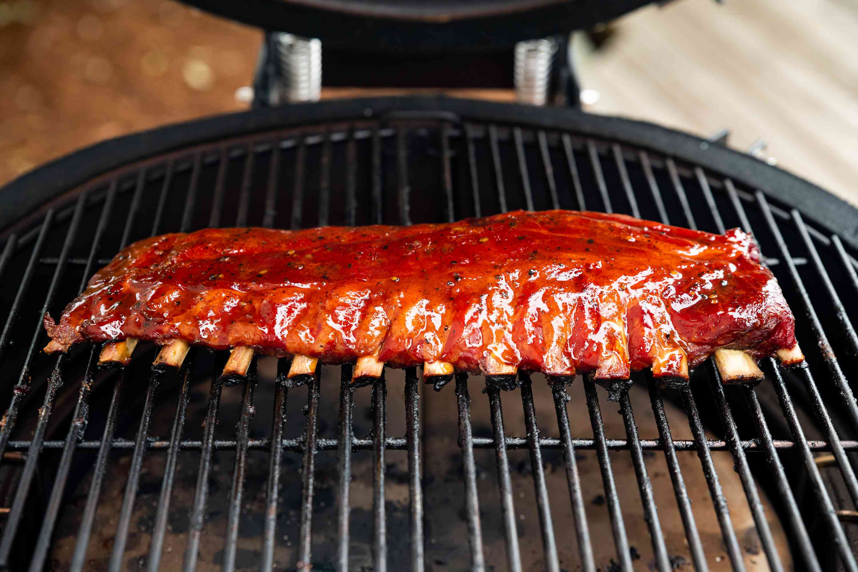ribs covered with sauce on the grill