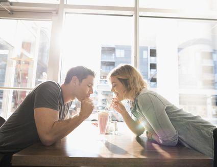 couple sharing milkshake drinking through separate straws
