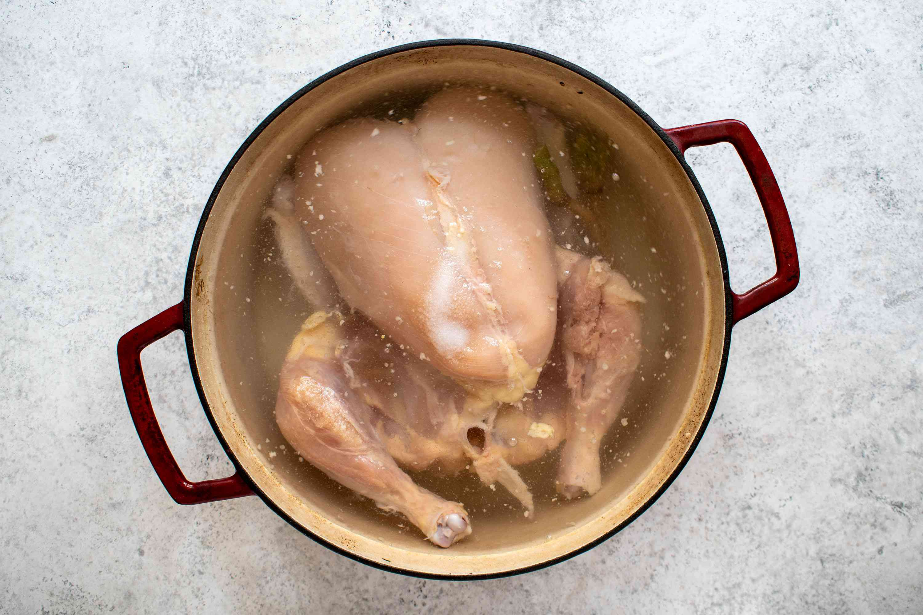 whole chicken boiling in a pot