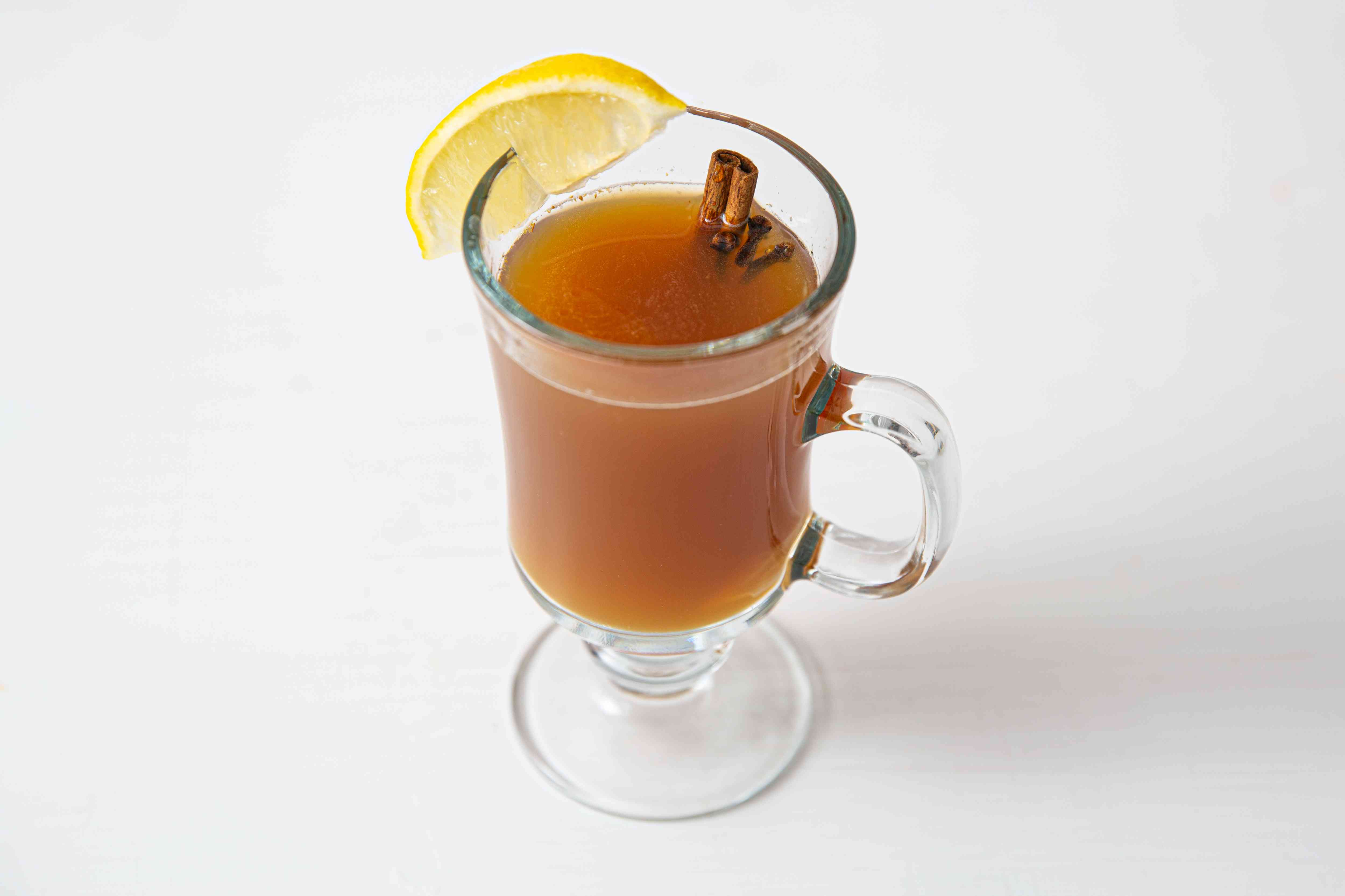 Hot apple toddy garnished with lemon and a cinnamon stick