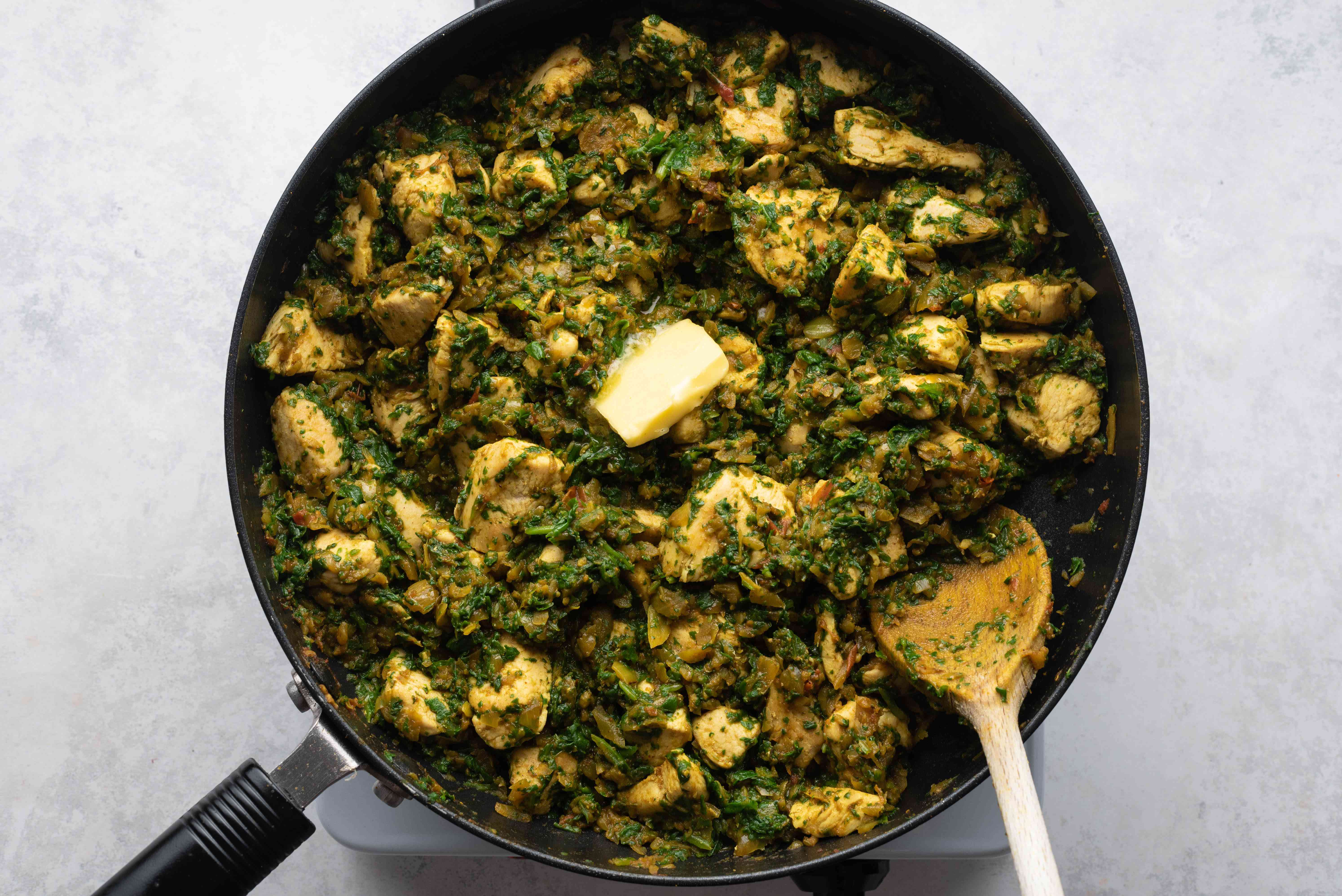 spinach and butter cooking with the chicken mixture in the pan
