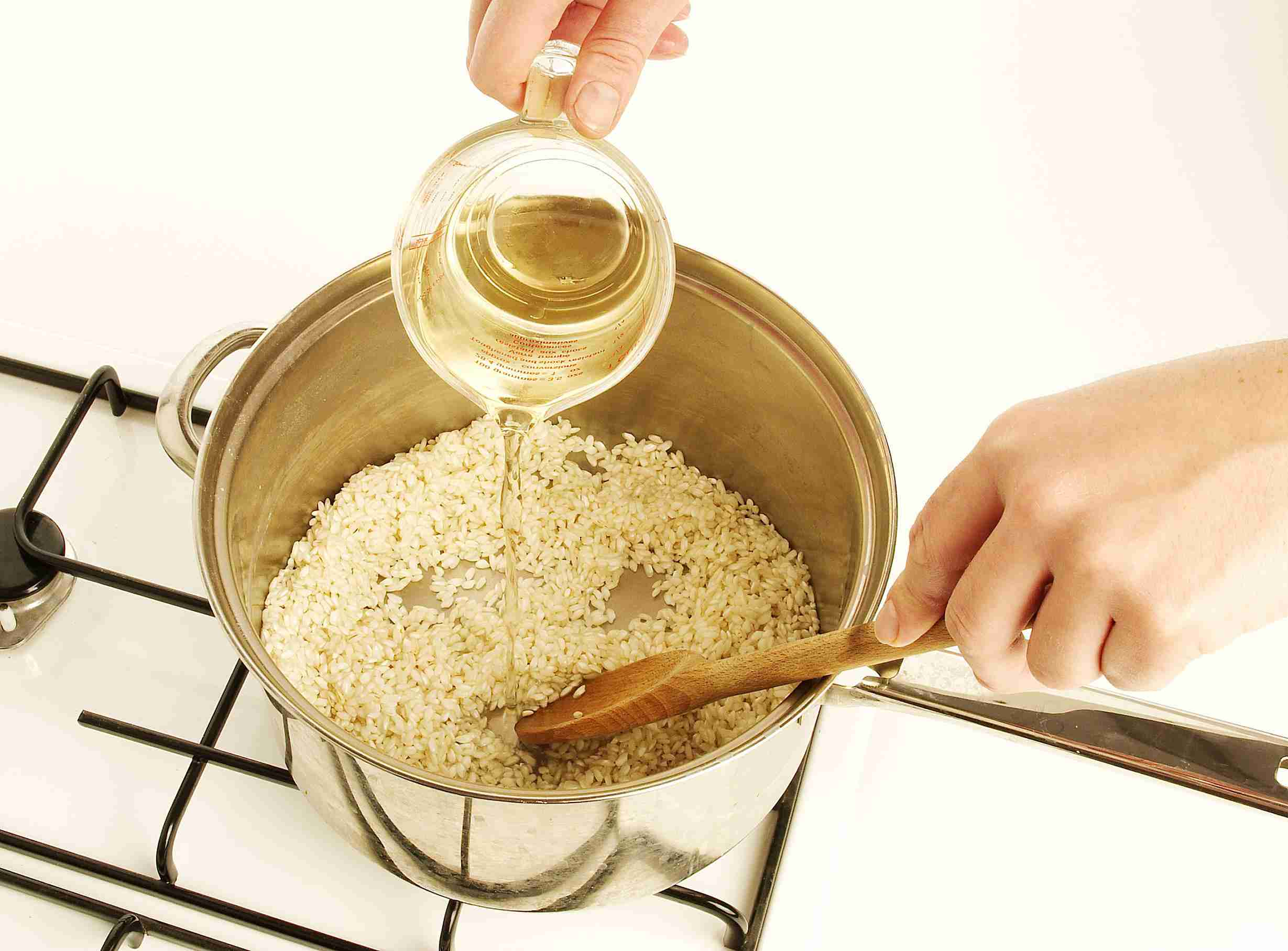 Hand pouring water into pot with rice