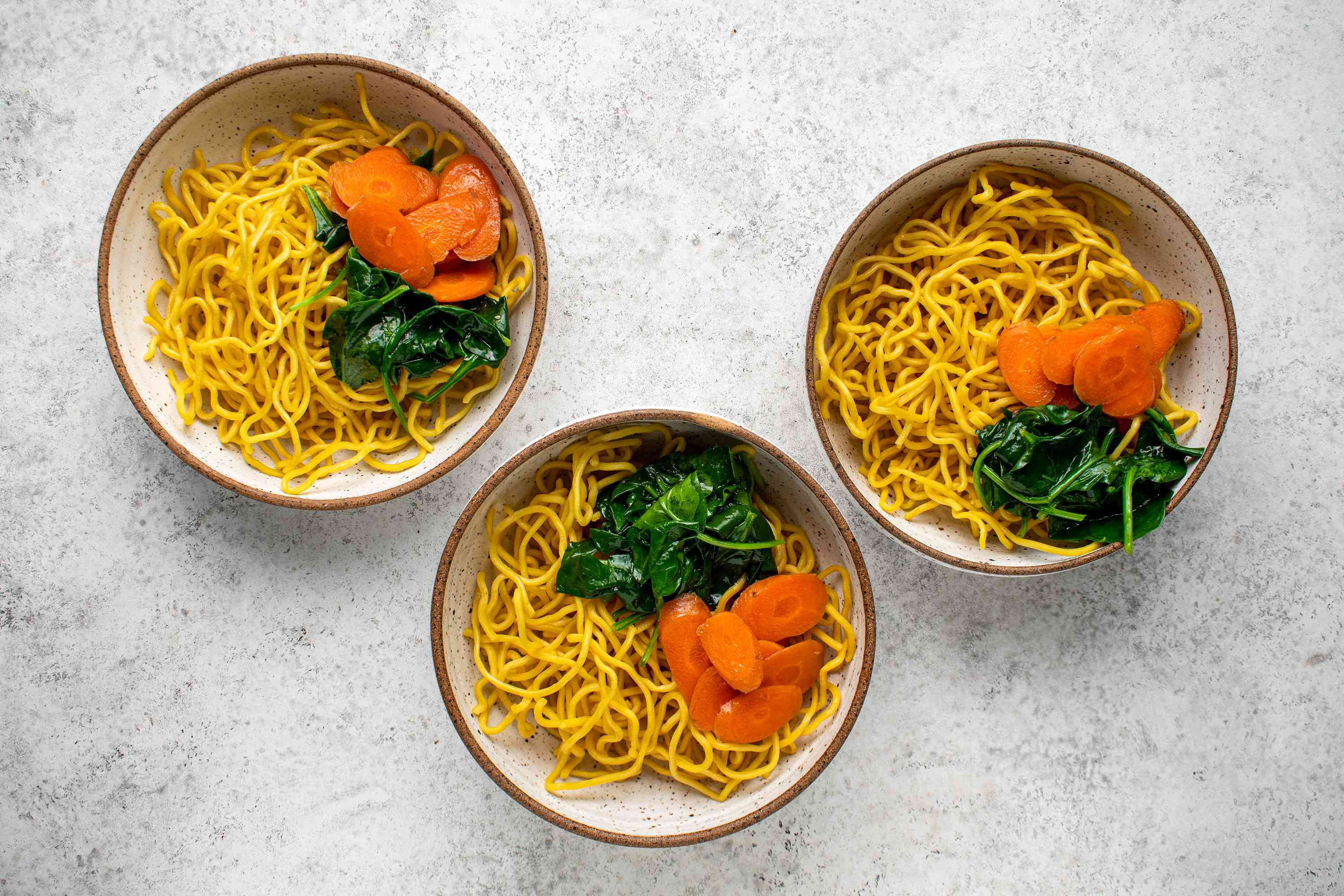Divide the carrot slices and spinach into three portions and put in the bowls