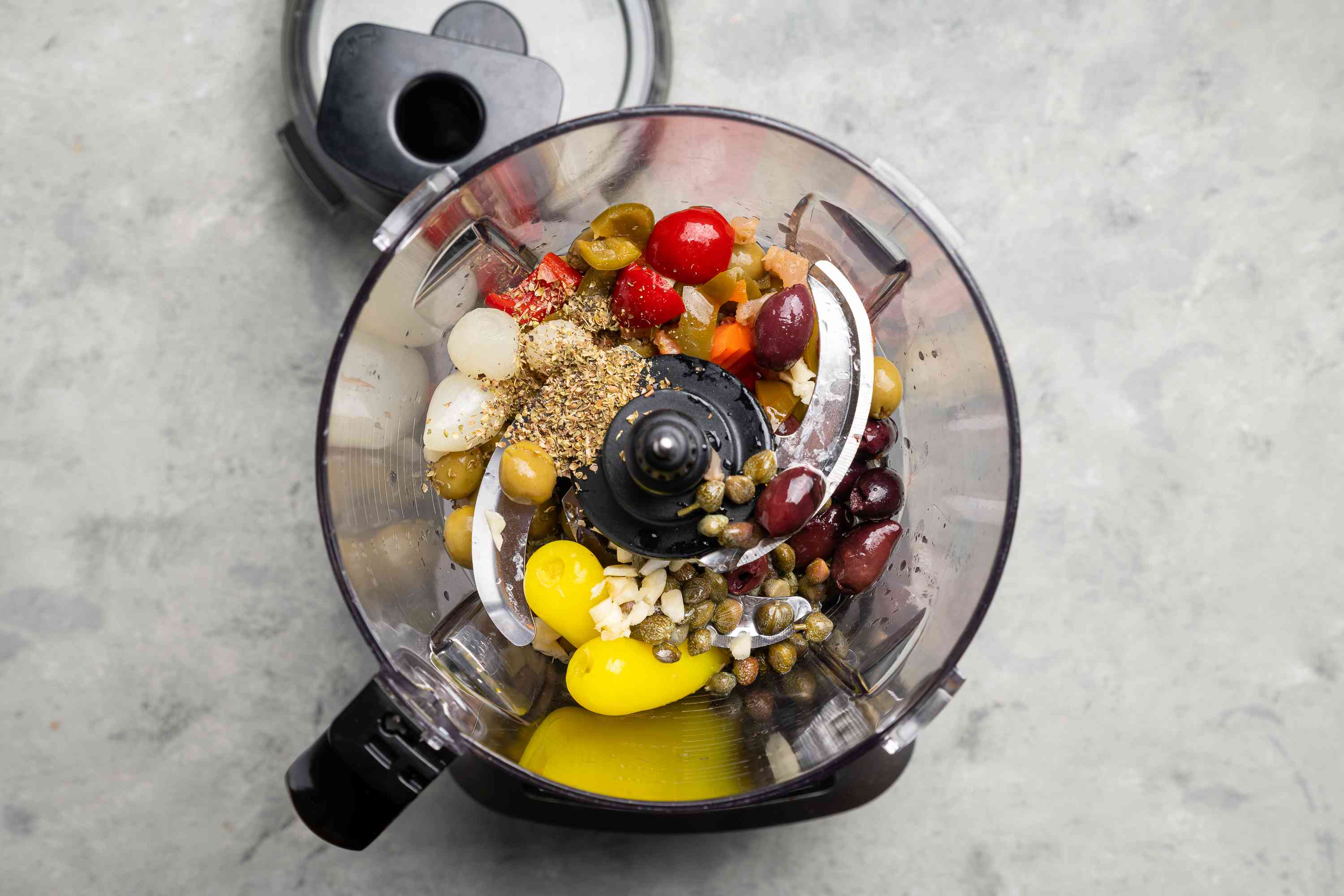 Drained ingredients in a food processor along with garlic, oregano, pepper, lemon juice, and olive oil