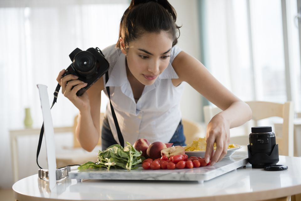 Hispanic woman photographing food