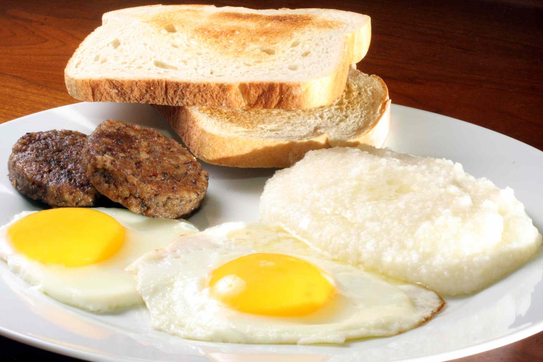 Breakfast of two fried eggs, sausage, grits and toast